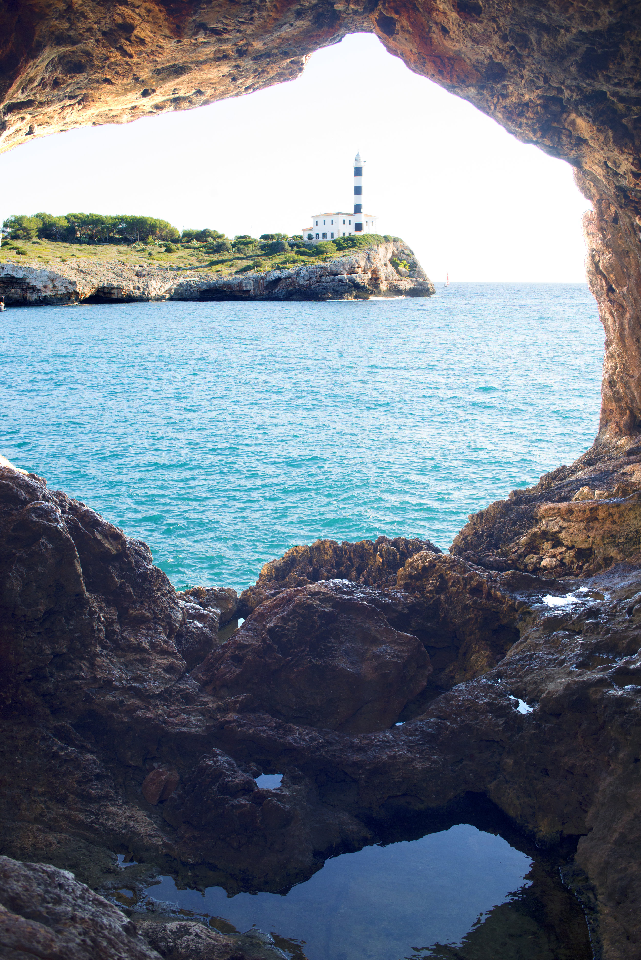 Lighthouse at Ponta de Ses Crest. Photographed from Natural Arch at Portocolom.