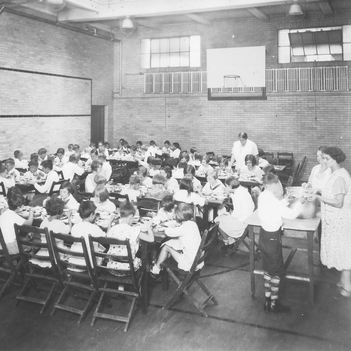 1924 Kids Eating Lunch in Gym.jpg