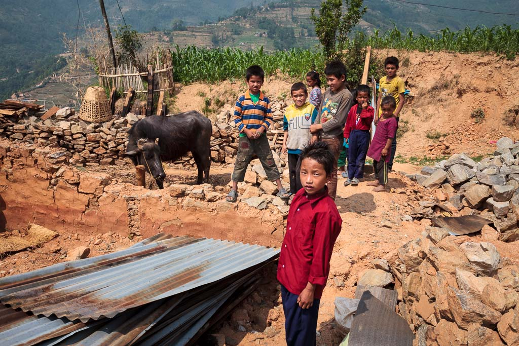 Young boy stands in the rubble of his stone and mud house on the arrival of the Moving Mountain School bag team to distribute bags to the young students many of whom lost family members and their homes on the same day.