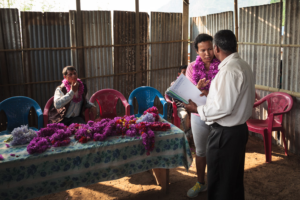 Rewati Gurung talks with one of the event organisers before distributing the school bags.
