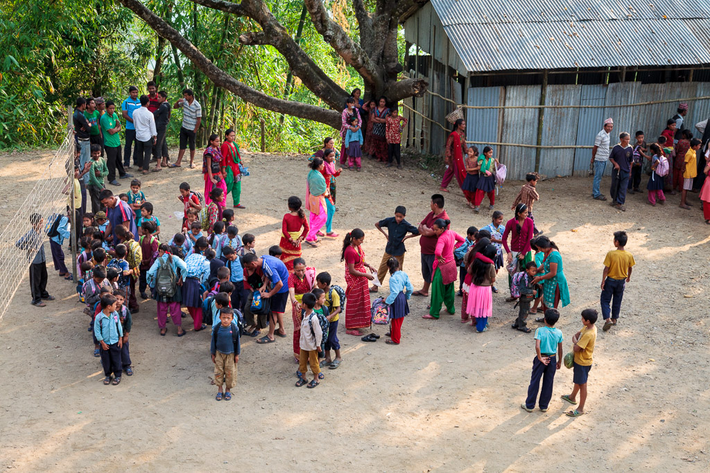 The school children who received their school bags gather in the playground.