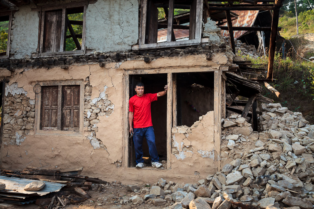A man stands in the doorway of his shattered house in Thakani, Sindupalchowk.