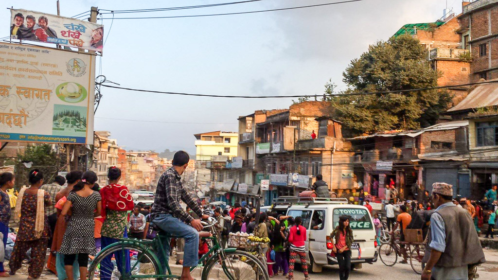 A man sits on top of a local bus with two gas bottles - a rare sight these days in Kathmandu.