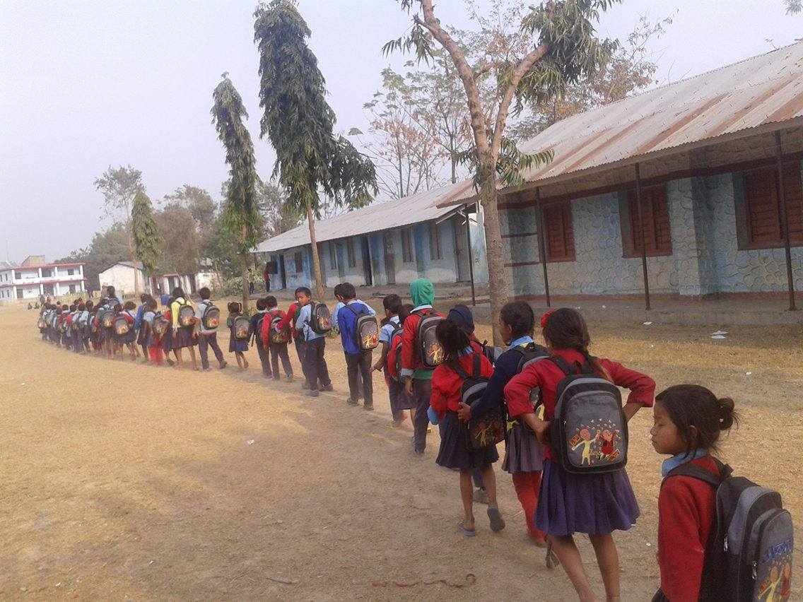 Children in Dudhauli walk in a line after school with Moving Mountain School Bags.