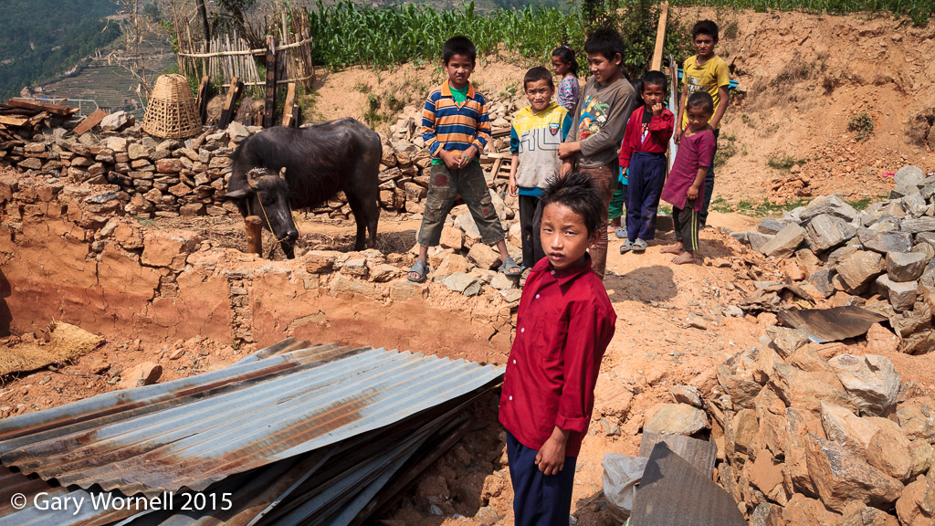 Children of Thakani, Sindupalchok, stand in the rubble of their home, May 19, 2015.