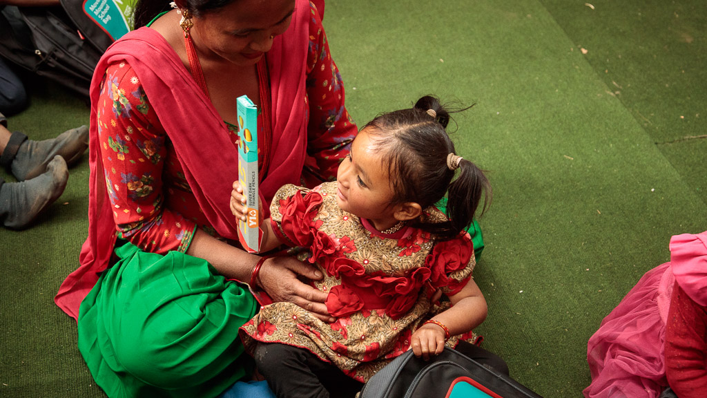 A young girl examines the contents of her new school bag in her mother's lap on donation day inside the old school