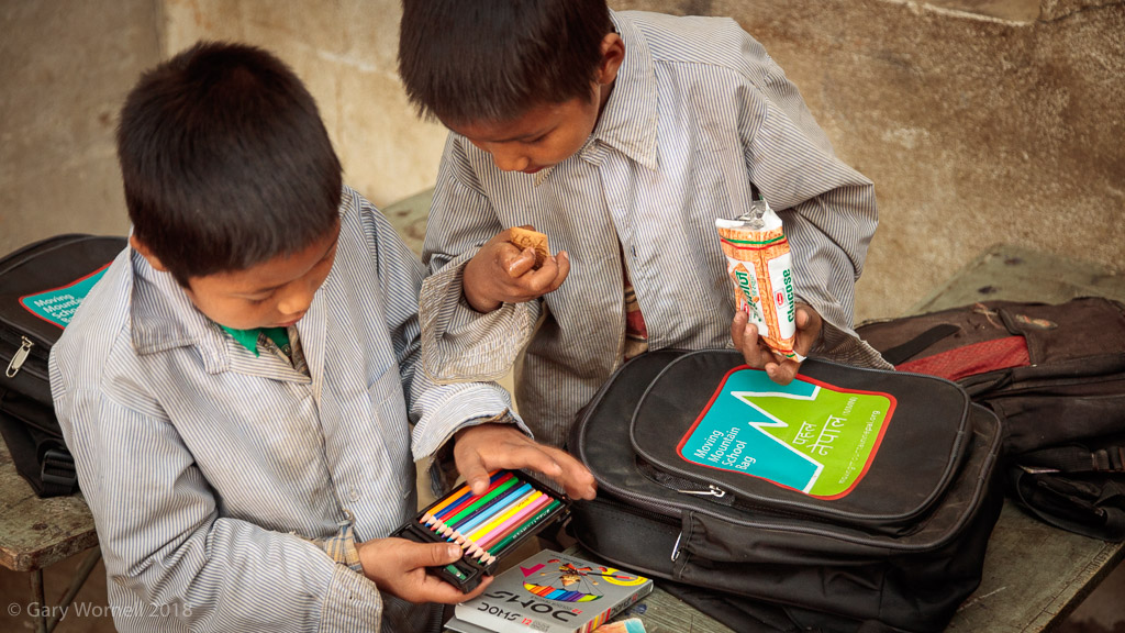 Two boys examine the contents of their new school bags.
