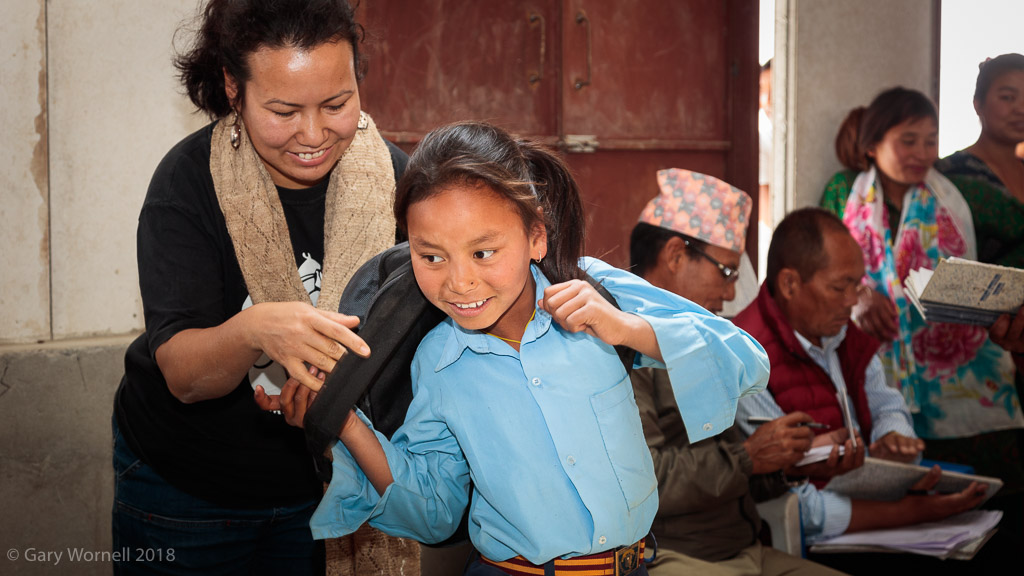 Founder of Moving Mountain Nepal Rewati Gurung helps a young student on with her new school bag.