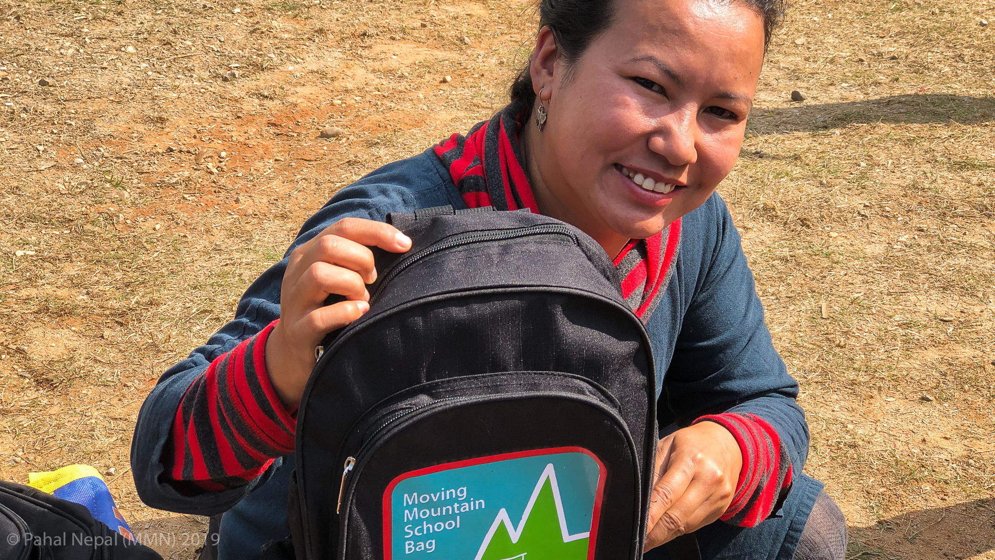 Rewati Gurung - founder of Moving Mountain Nepal shows the latest school bag. Since the early days the bag has been developed by our bag maker in Kathmandu to be robust and waterproof capable of lasting the student for many years.