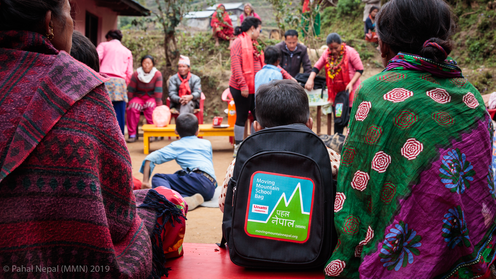 A young student sits on a bench beside his mother as the bag donation program continues at Bhumistan Basic School in Dhading.