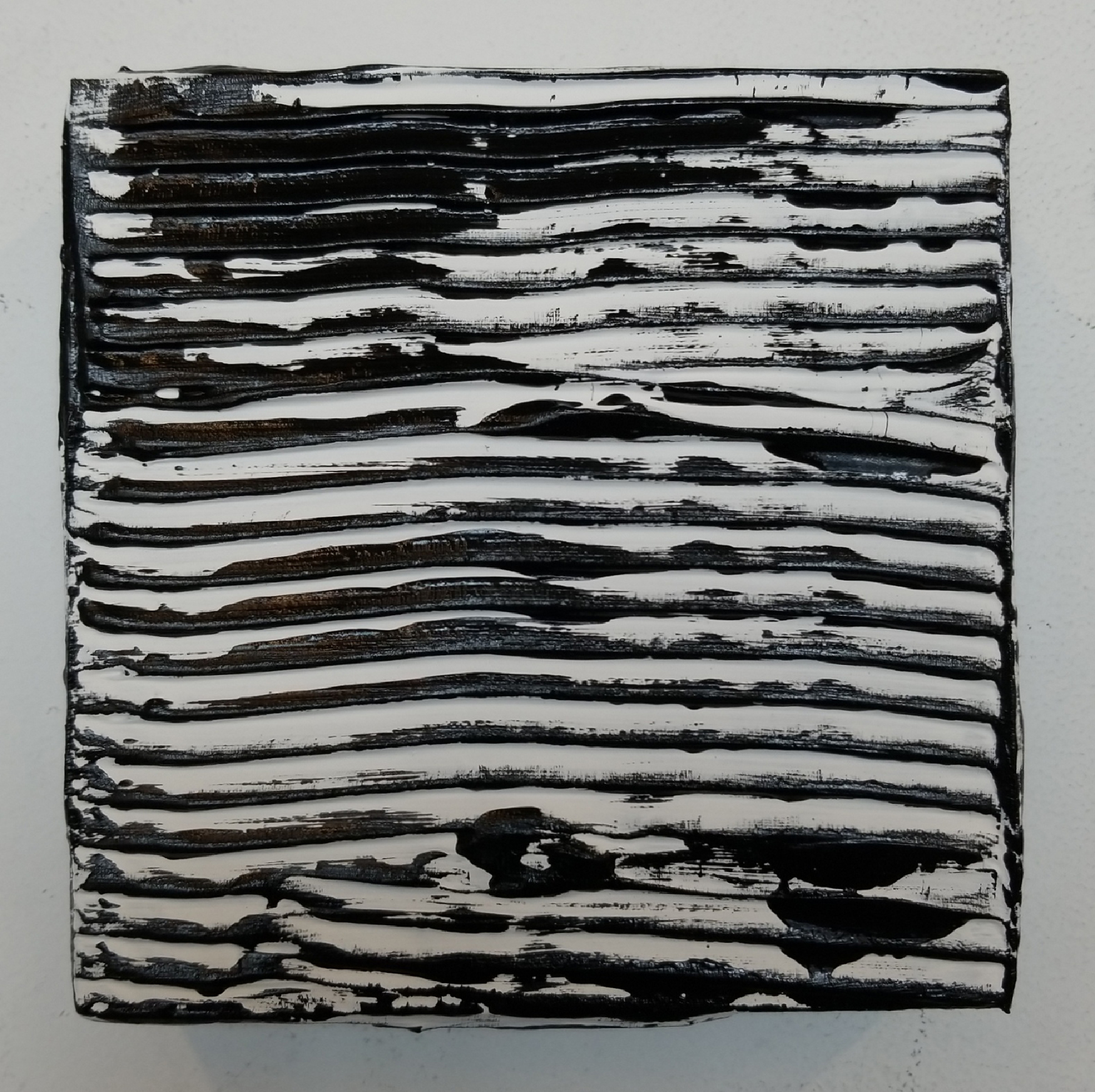 "Wayson R. Jones, ""Newsprint,"" 2018, fine-ground pumice gel, gesso, carbon black acrylic paint on wood panel, 6 x 6 x1.5 inches. Image courtesy the artist."