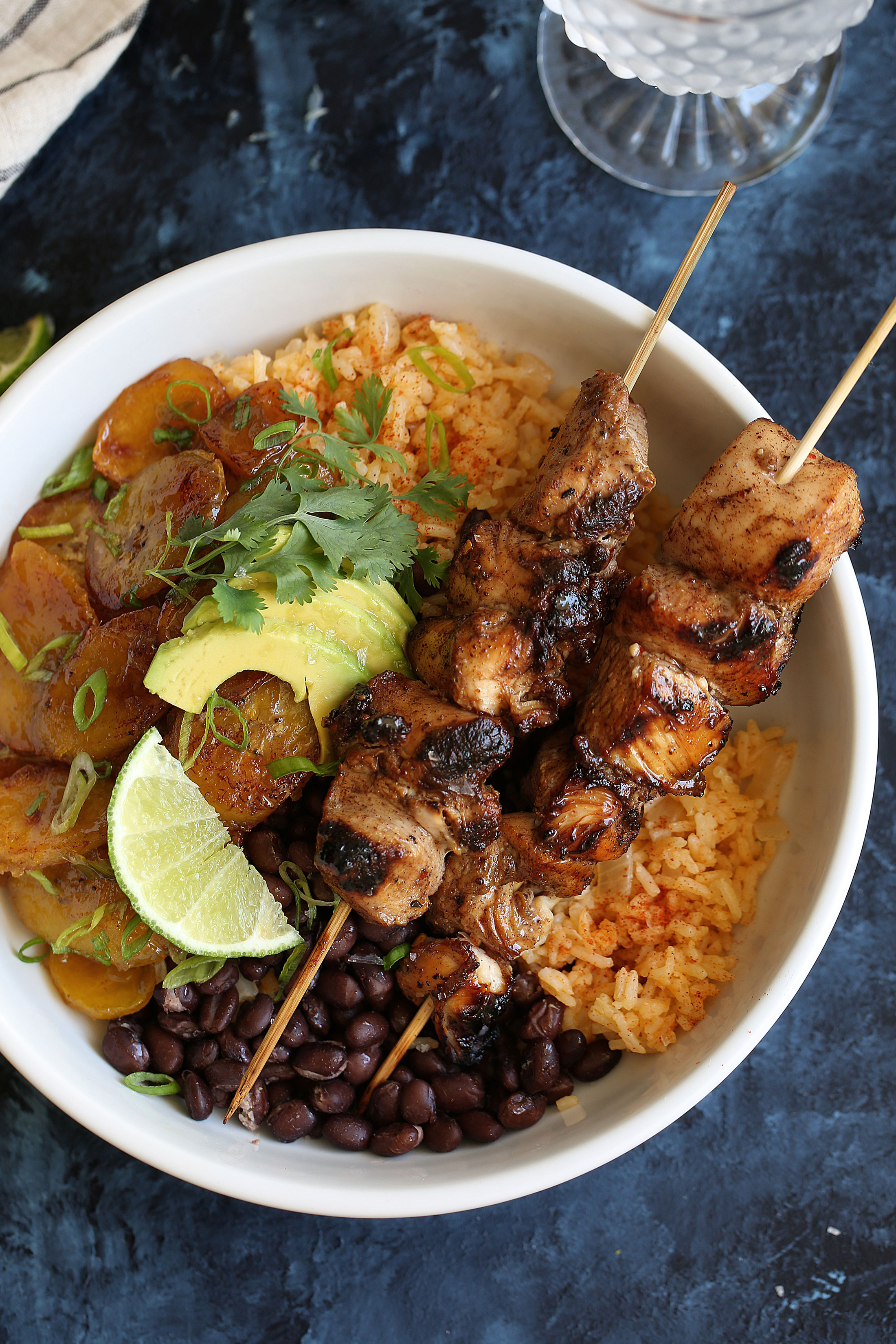 jerk chicken skewers with sweet plantains, yellow rice and black beans