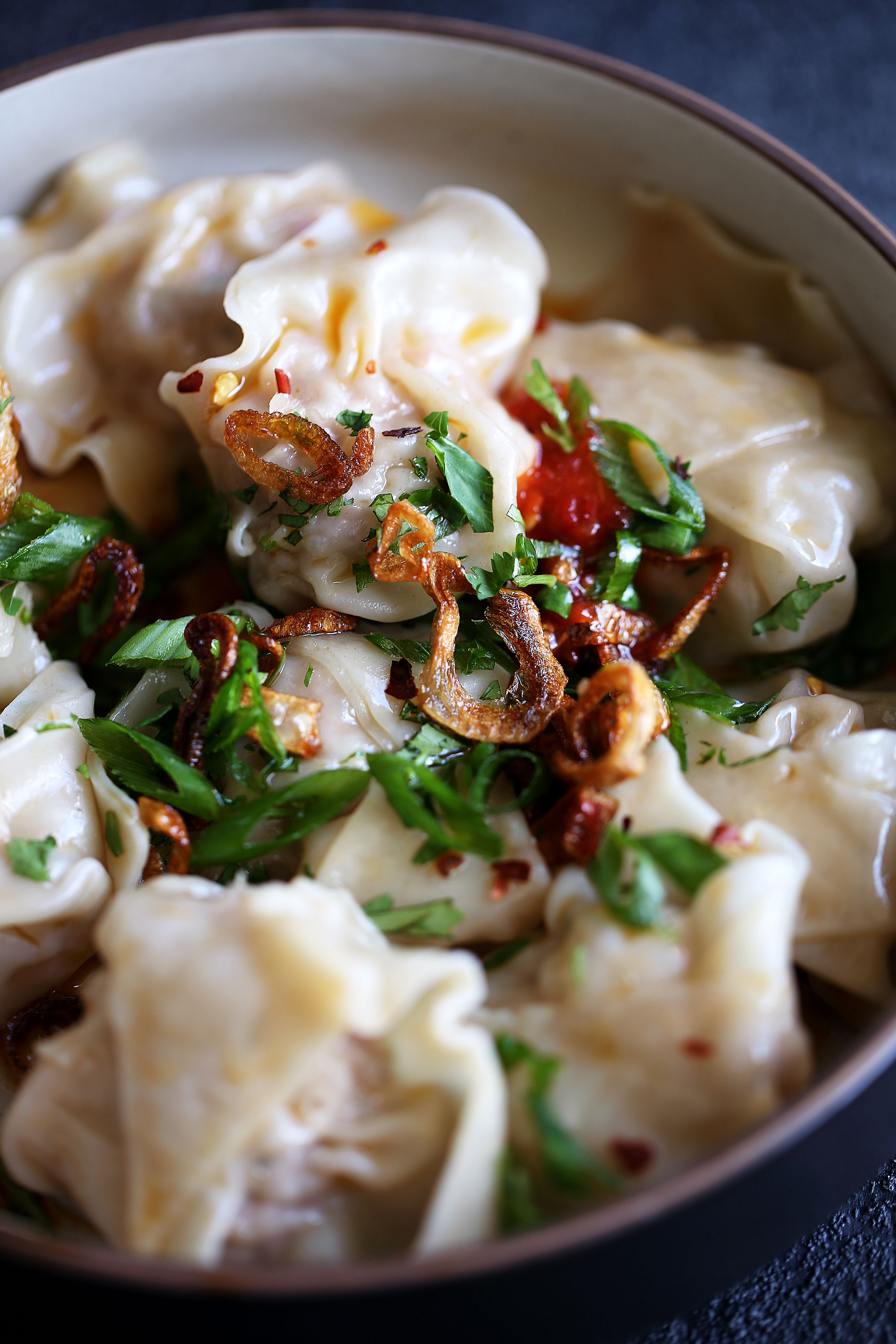 spicy sichuan wontons with chili sauce closeup