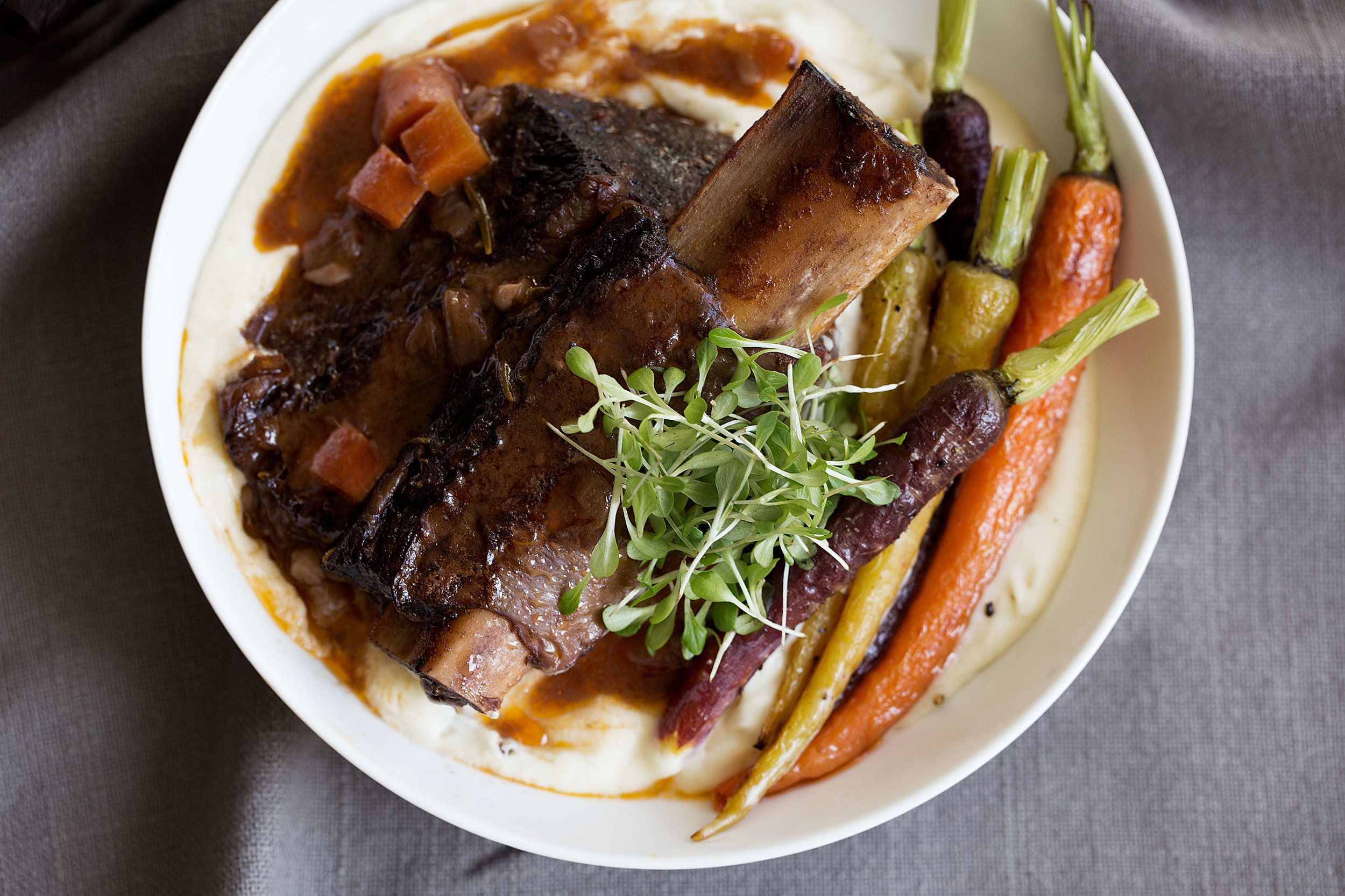 braised short ribs with celery root purée closeup bowl and roasted carrots