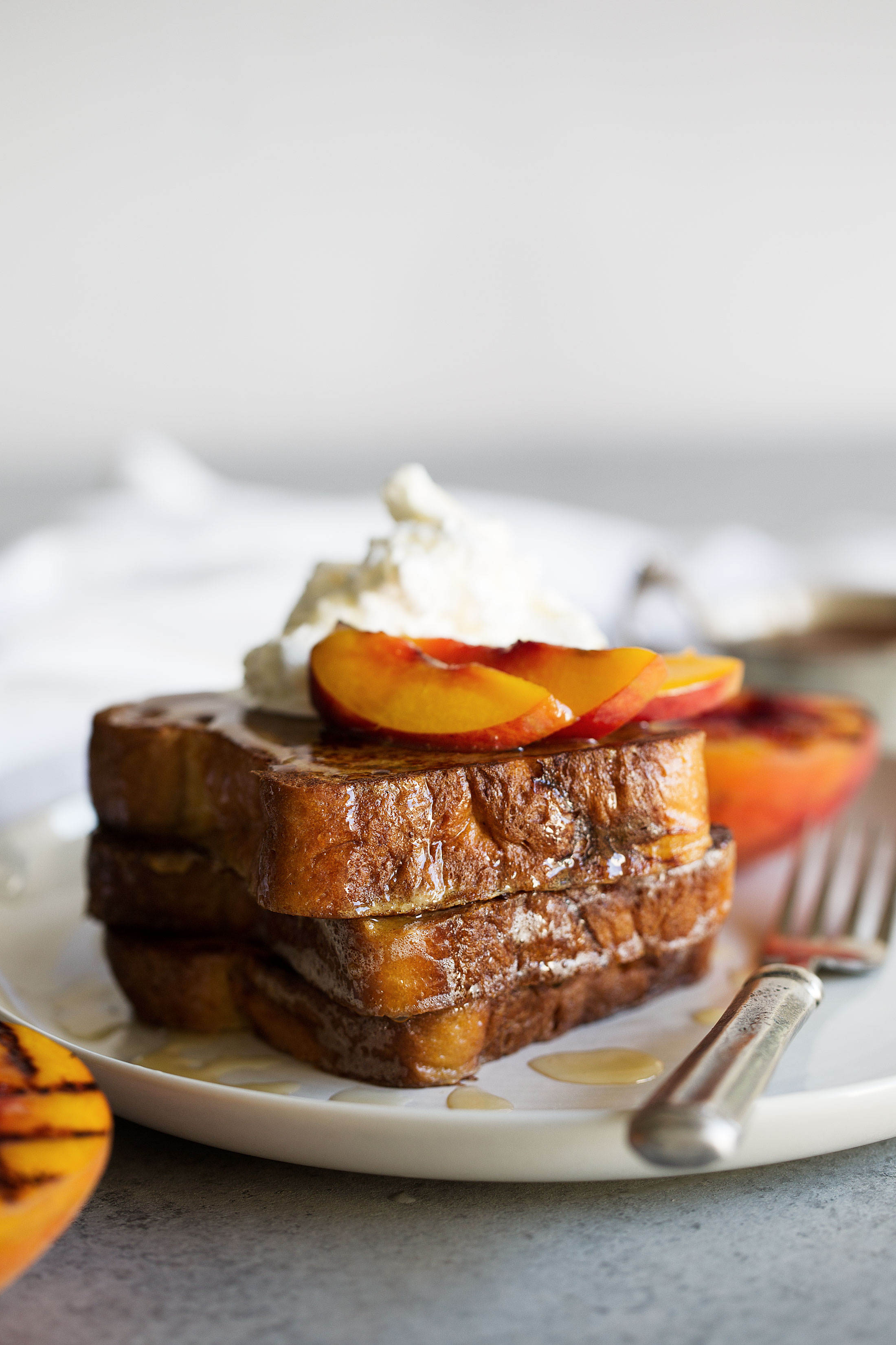 Grilled peaches and cream challah french toast cooking with cocktail rings