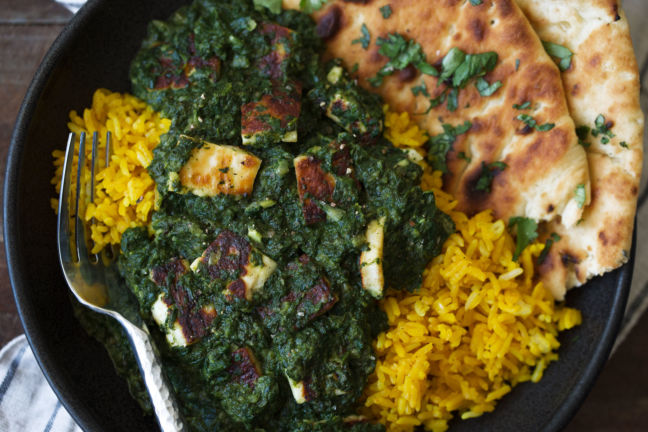 saag paneer over turmeric rice closeup cooking with cocktail rings