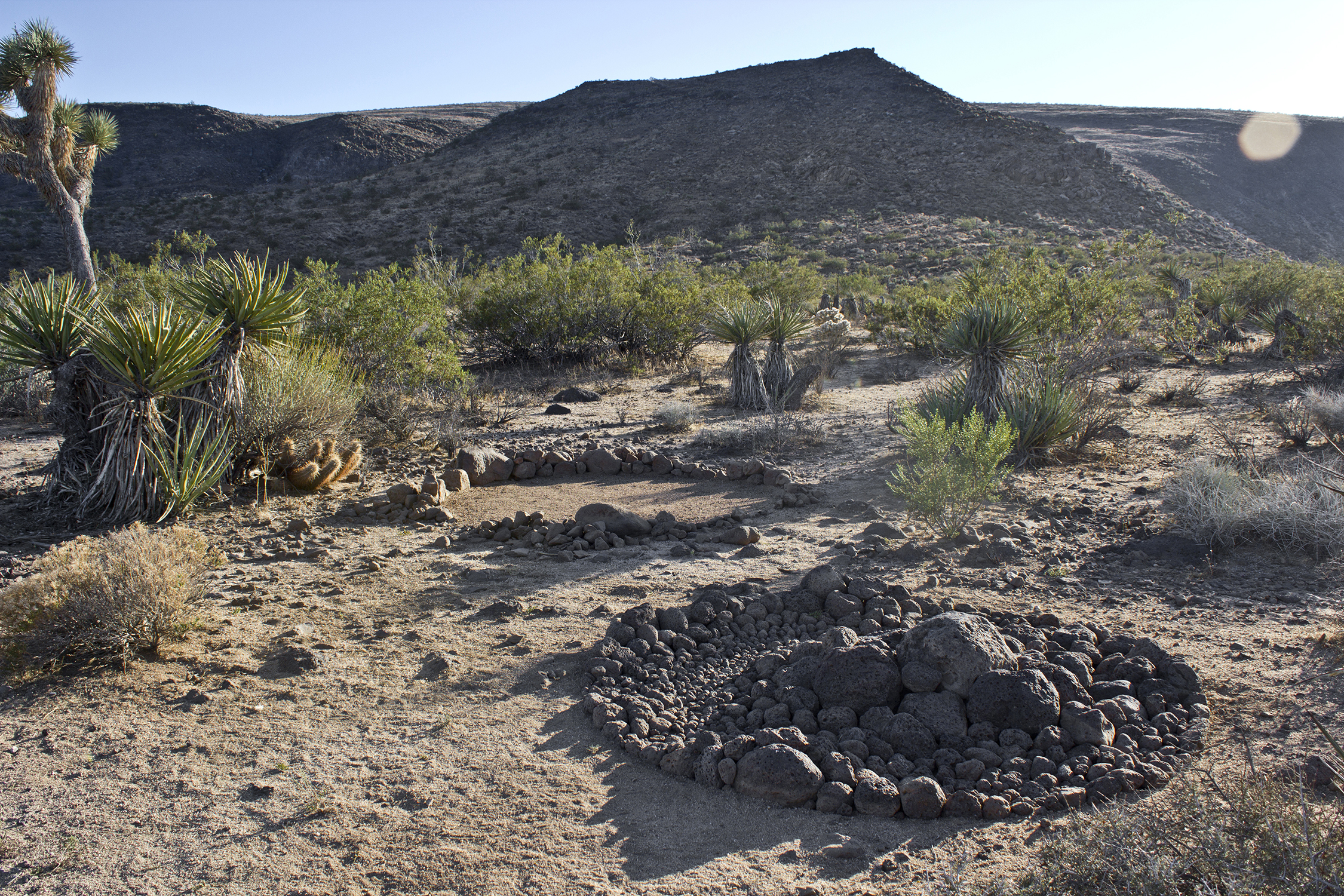"""Nocturnal Animals / Janus""   Materials: lava rocks was created in 2017 by  Andres Payan-Estrada  an the five acre JEMEZ HOMESTEAD : STOLEN LAND art project in Flamingo Heights at the foot of Flat Top Mesa. The re-arrangement of rocks and sand sits on the border of the  Sand to Snow National Monument Black Lava Butte and Flat Top Mesa addition, an approximately rectangular area 3 by 3.5 miles in extent, containing two broad, volcanic mesas;  Black Lava Butte  to the west and  Flat Top  to the east. They rise 250 feet above the surrounding desert plains, along the west side of Homestead Valley, north of the town of Yucca Valley, and all the area is easily reached from paved roads along the south and east sides."