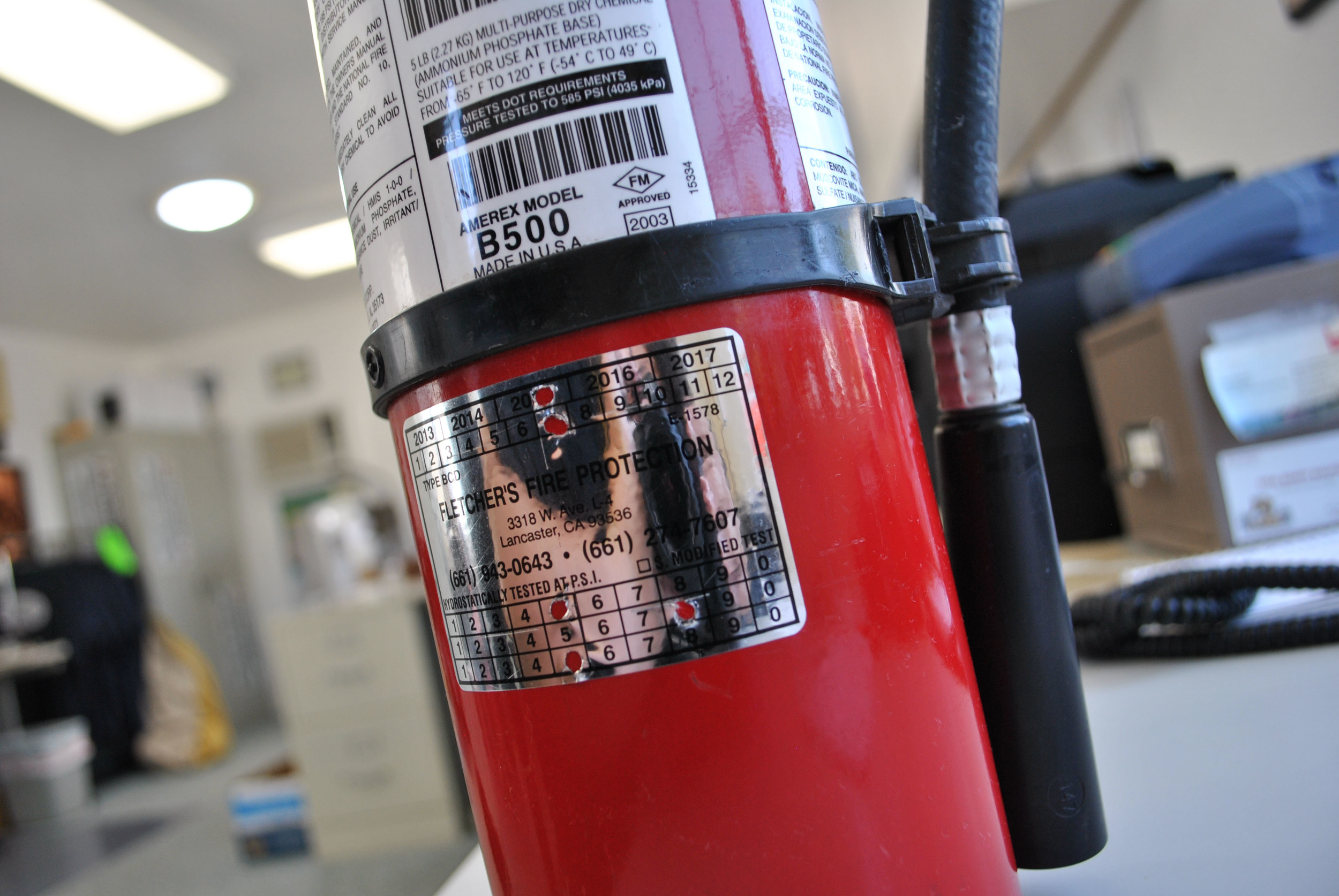 This fire extinguisher is 12 years old and so requireda hydro test. The back of the extinguisher with its hydro test sticker is pictured here.