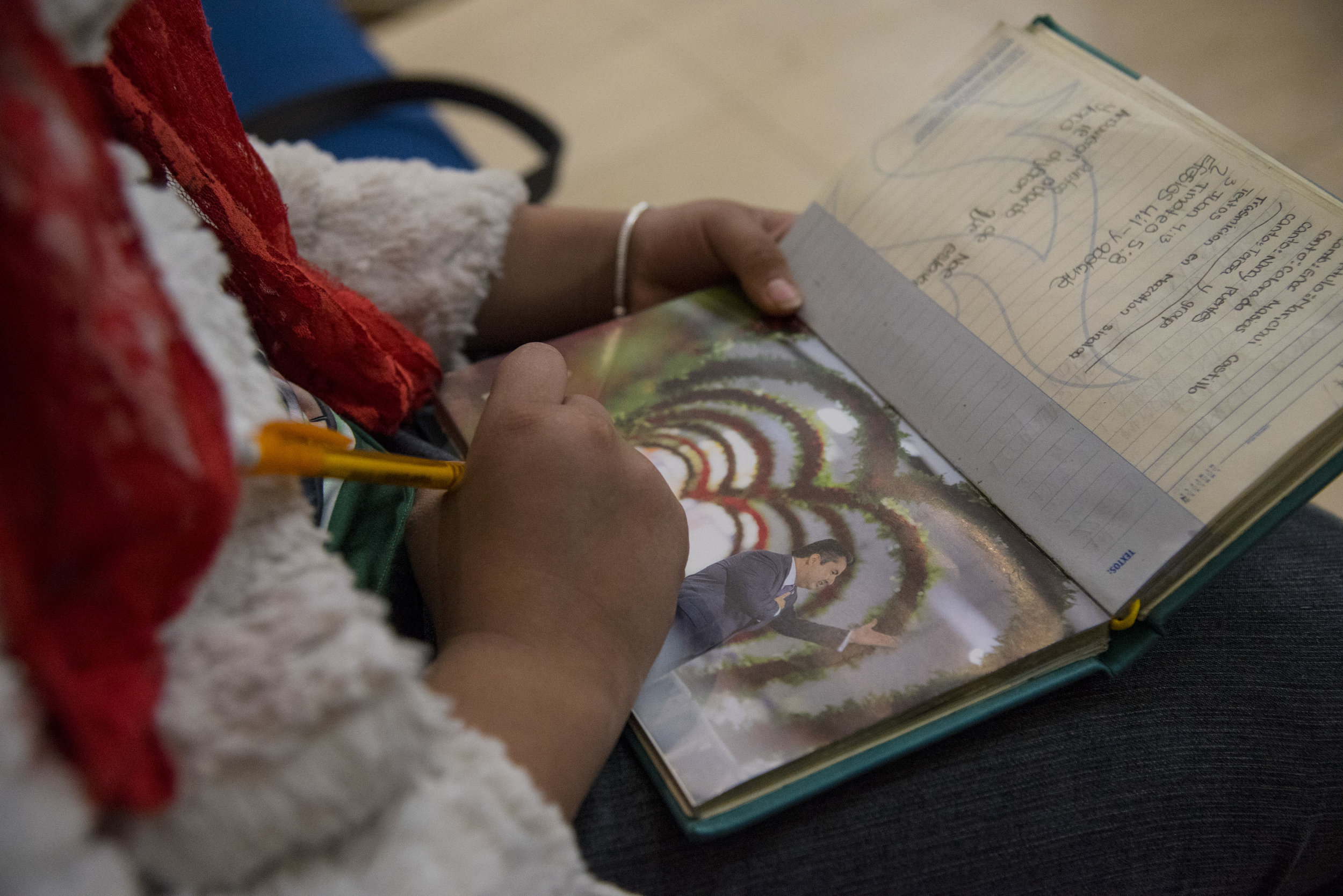 Hillary Guillen, 11, opens her notebook to her favorite picture of Naasón Joaquín García, the leader of the international Light of the World church. Members of the church believe that García is a Living Apostle called by God to lead His people during the restoration of the primitive church.