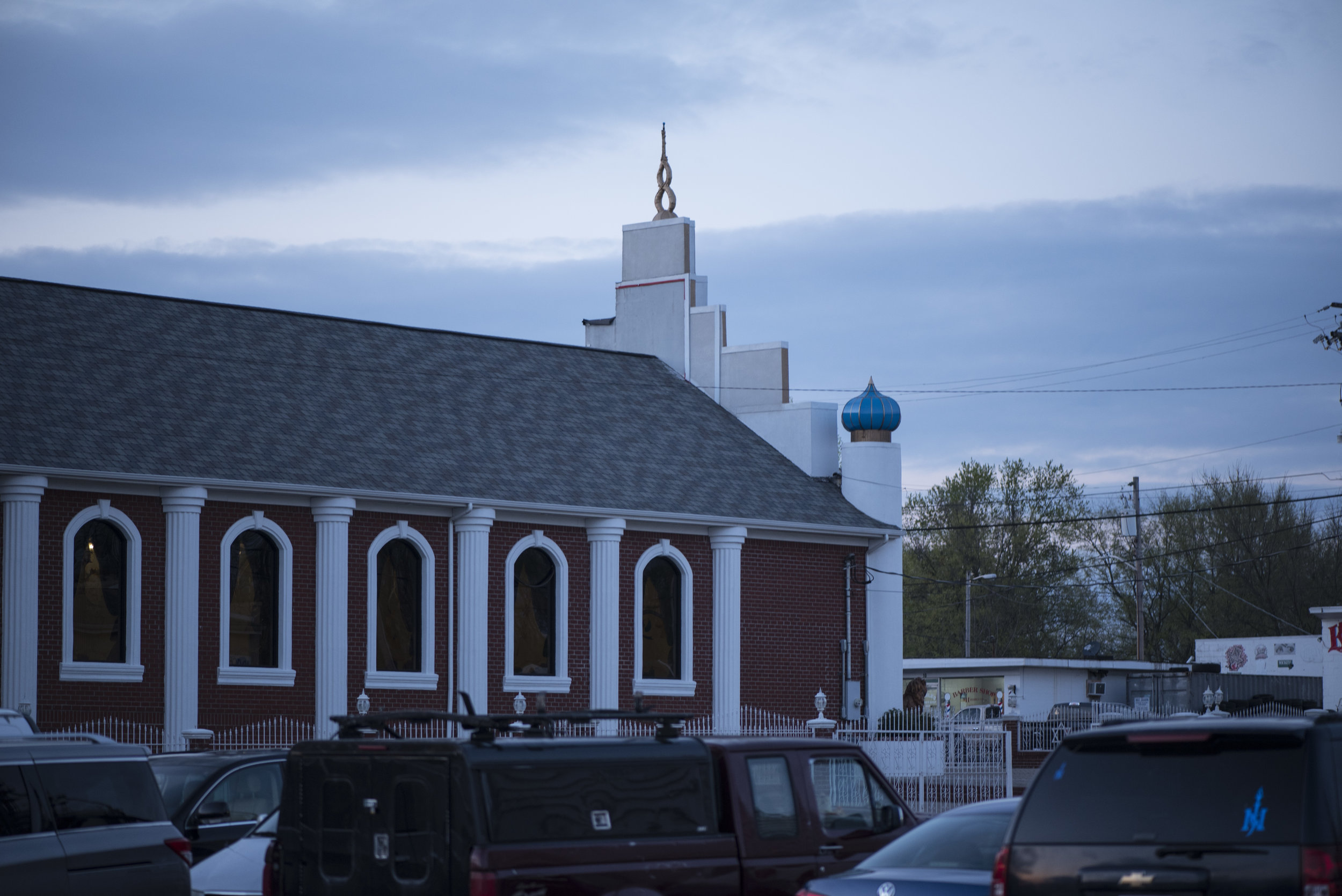 Vehicles sit vacant in a gravel parking lot off of Clay Street as owners and occupants worship across the street in the sanctuary of the Light of the World church.