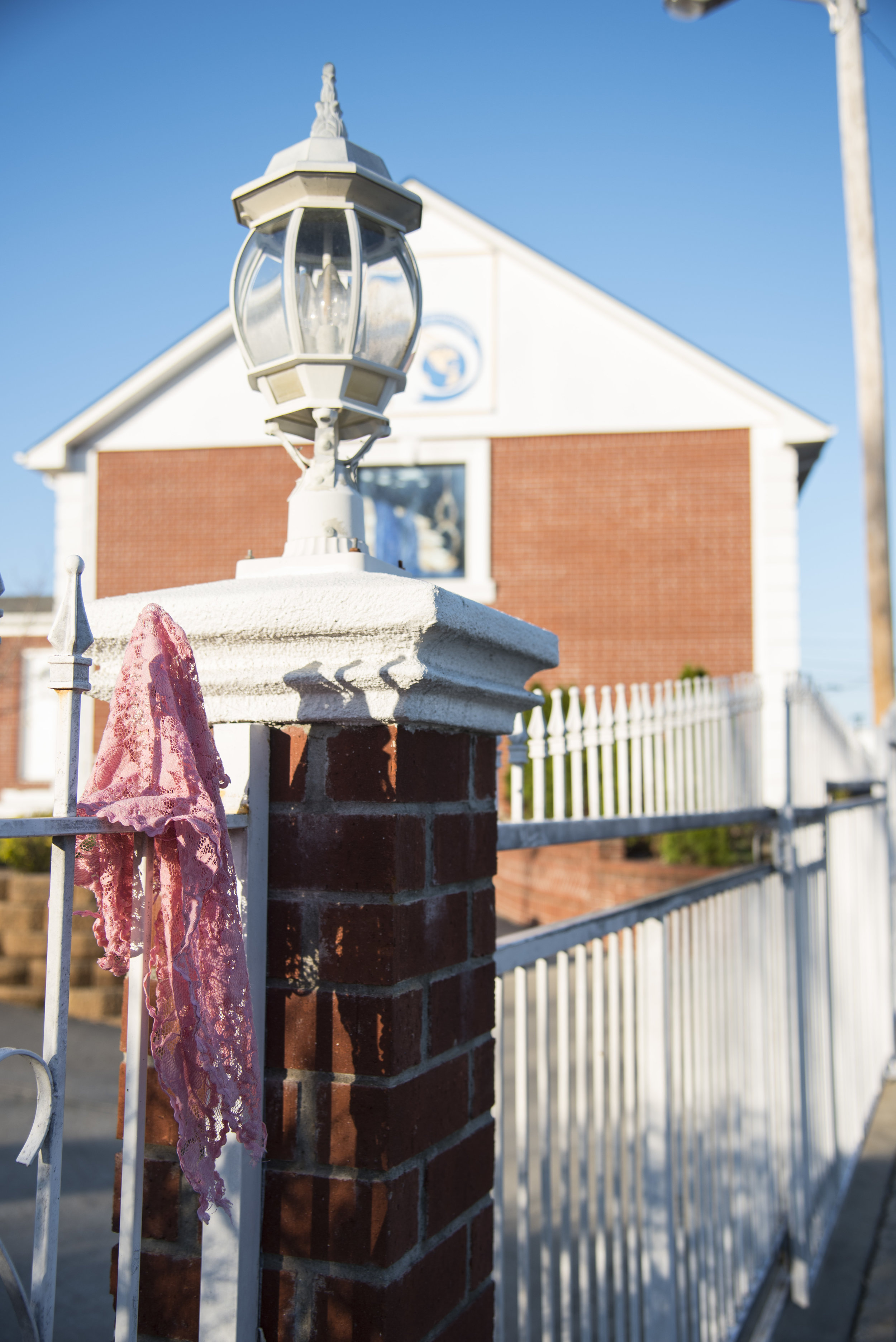 A pañuelo, or headscarf, hangs from the back gate of the Light of the World church courtyard. Women wear the pañuelos inside the sanctuary as a sign of humility.