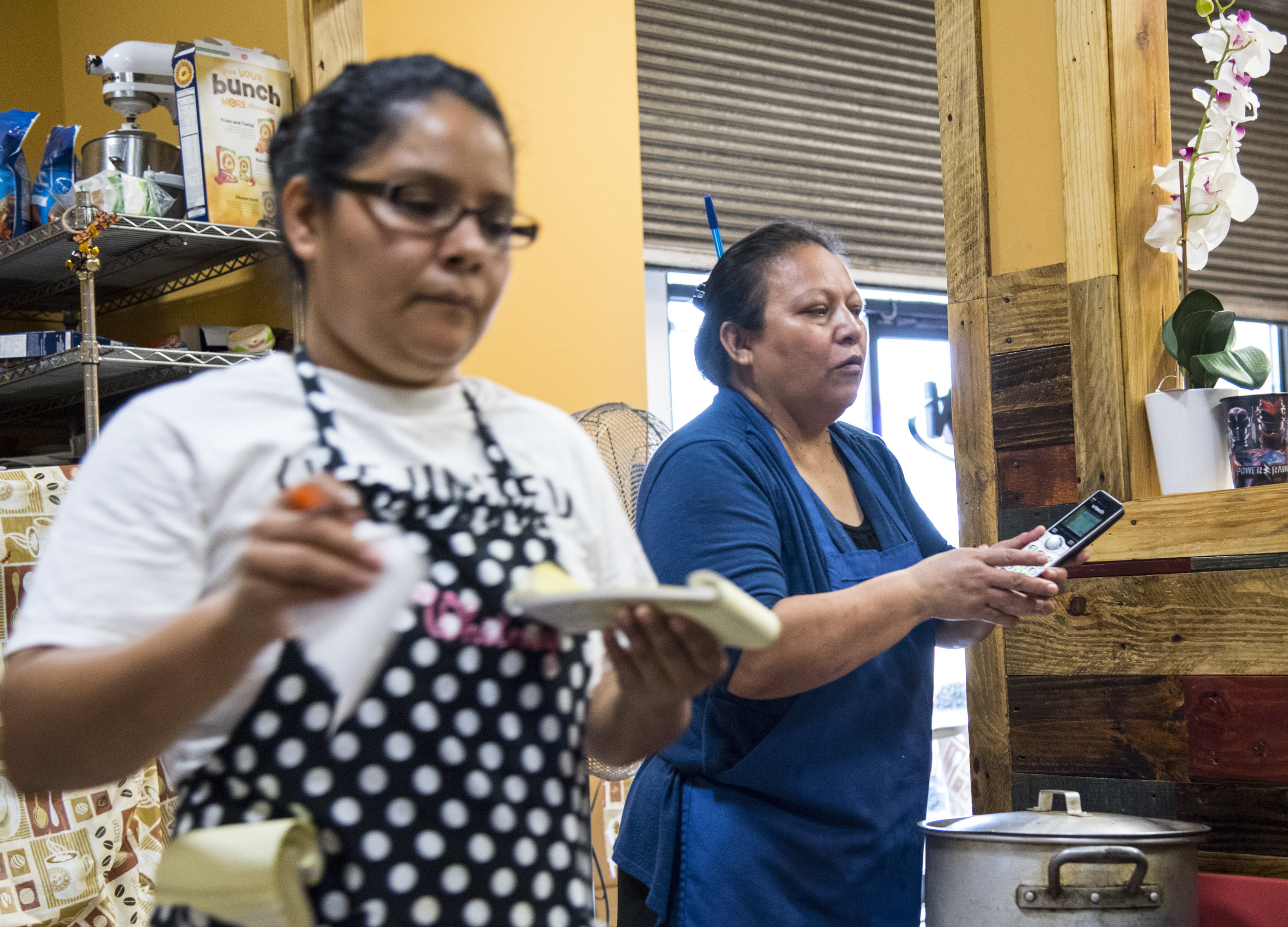 Irma Guillen, 49, finishes taking an order on the phone at La Perlita, the taquería where she volunteers her time. Guillen, her husband and their children are members of the church.