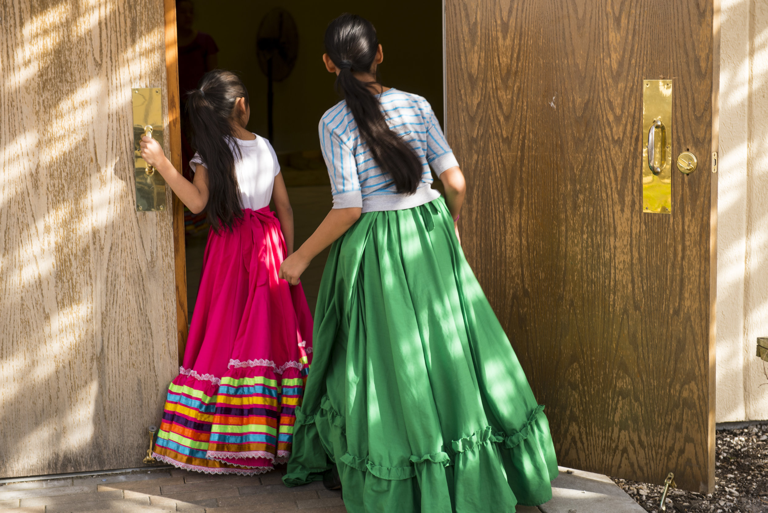 Dancers waiting for their turn to rehearse, watch another group practice in the building next to the taquería.