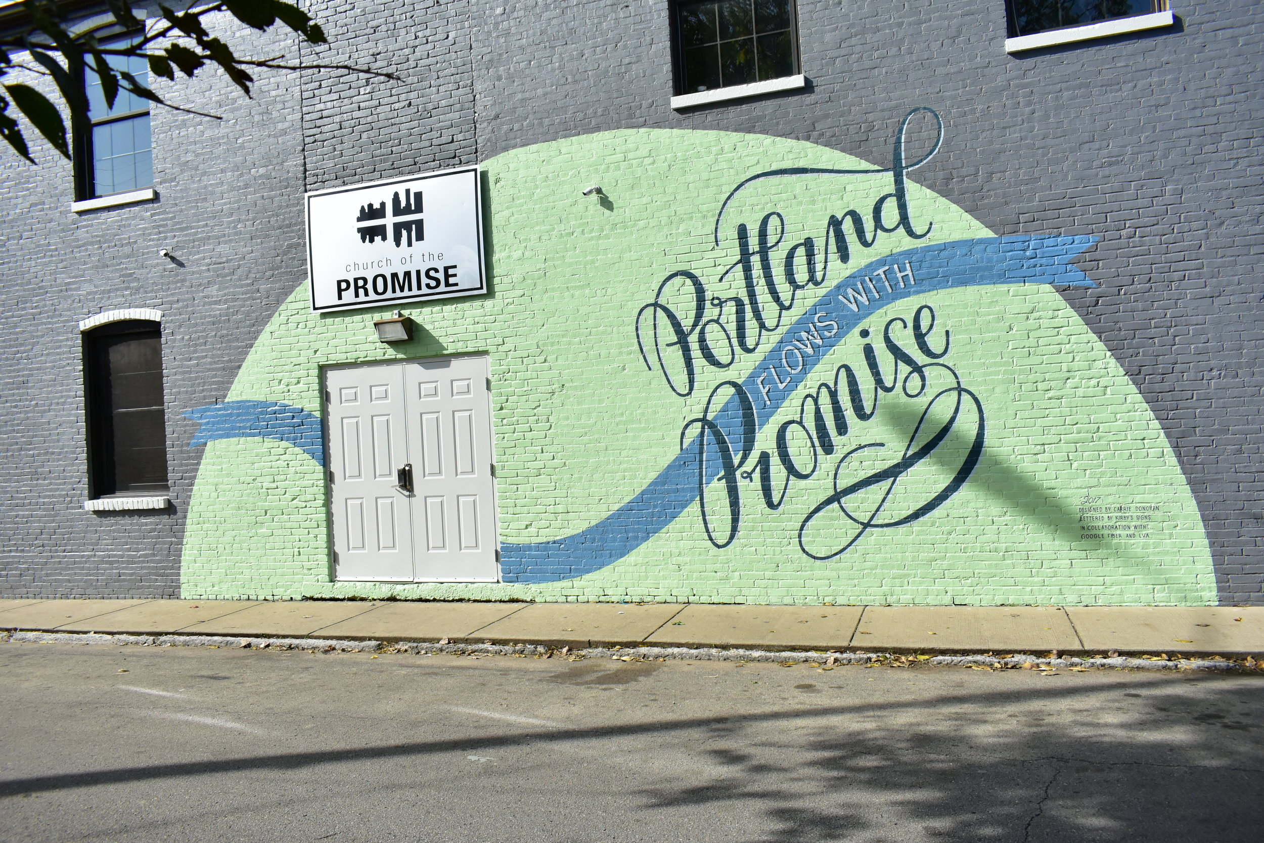 The elements of the mural visually connect the different aspects of what happens in the Promise Building, and the banner and the type express the idea of flow—like the river, and like the way their work flows into the community.
