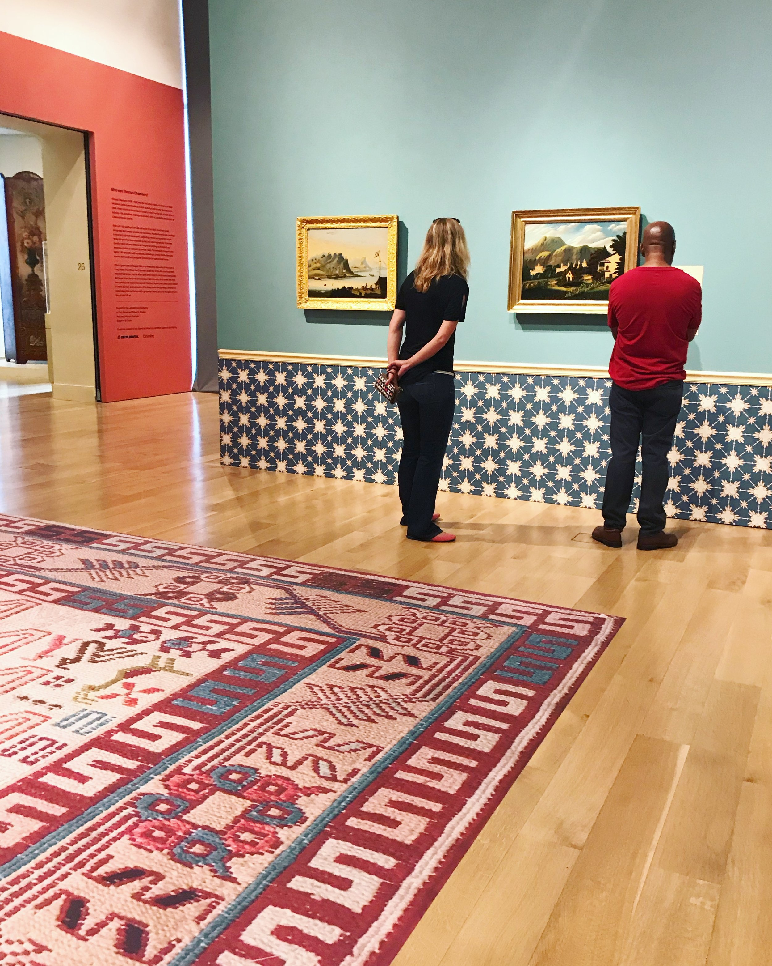 """The interior of the exhibition was designed in the style of """"American Fancy,"""" an over-the-top décor style popular in the period of Thomas Chambers. The space included a custom wallpaper pattern as well as photographs of rugs reproduced in vinyl on the floor."""