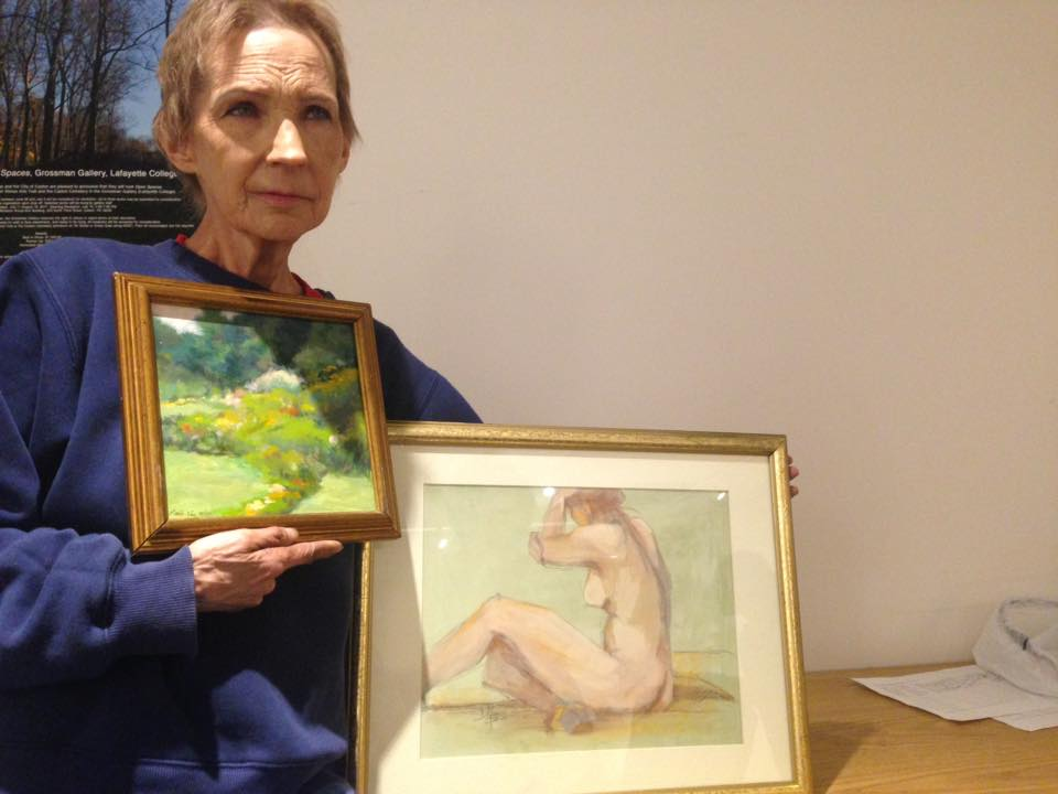 """Patti holding two donated paintings:""""A Pocketful of Roses"""" oil on board by  Li-hsien Price  $200 and also a figure painting by Donna Needs (sold)."""