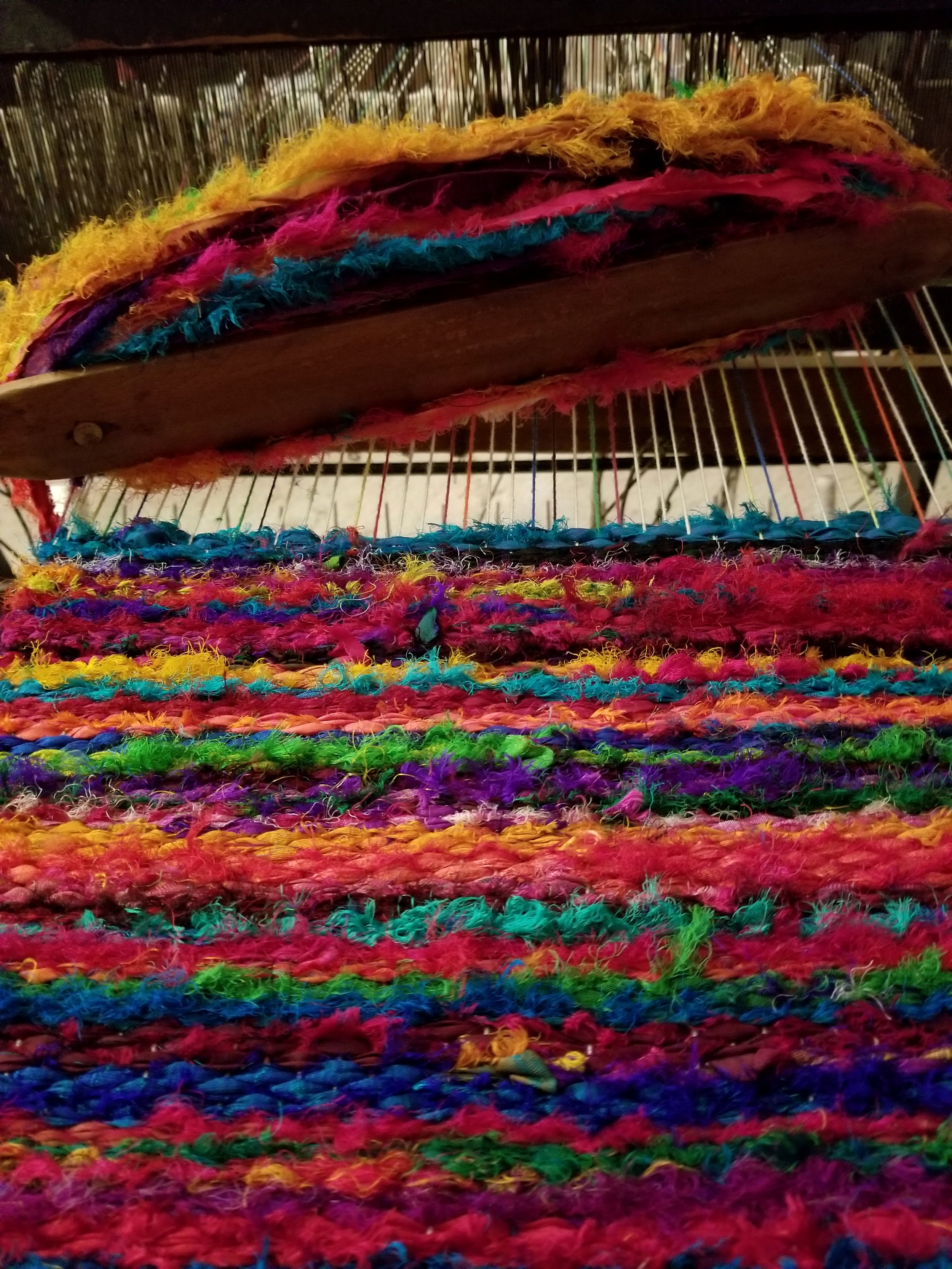 Sari Silk in the process of being woven on Lori's antique loom. WOW, look at that color!