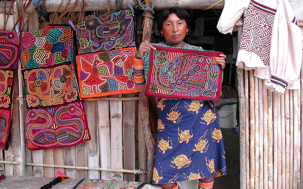 A Guna woman displays molas she created in front of her home in the San Blas Islands.