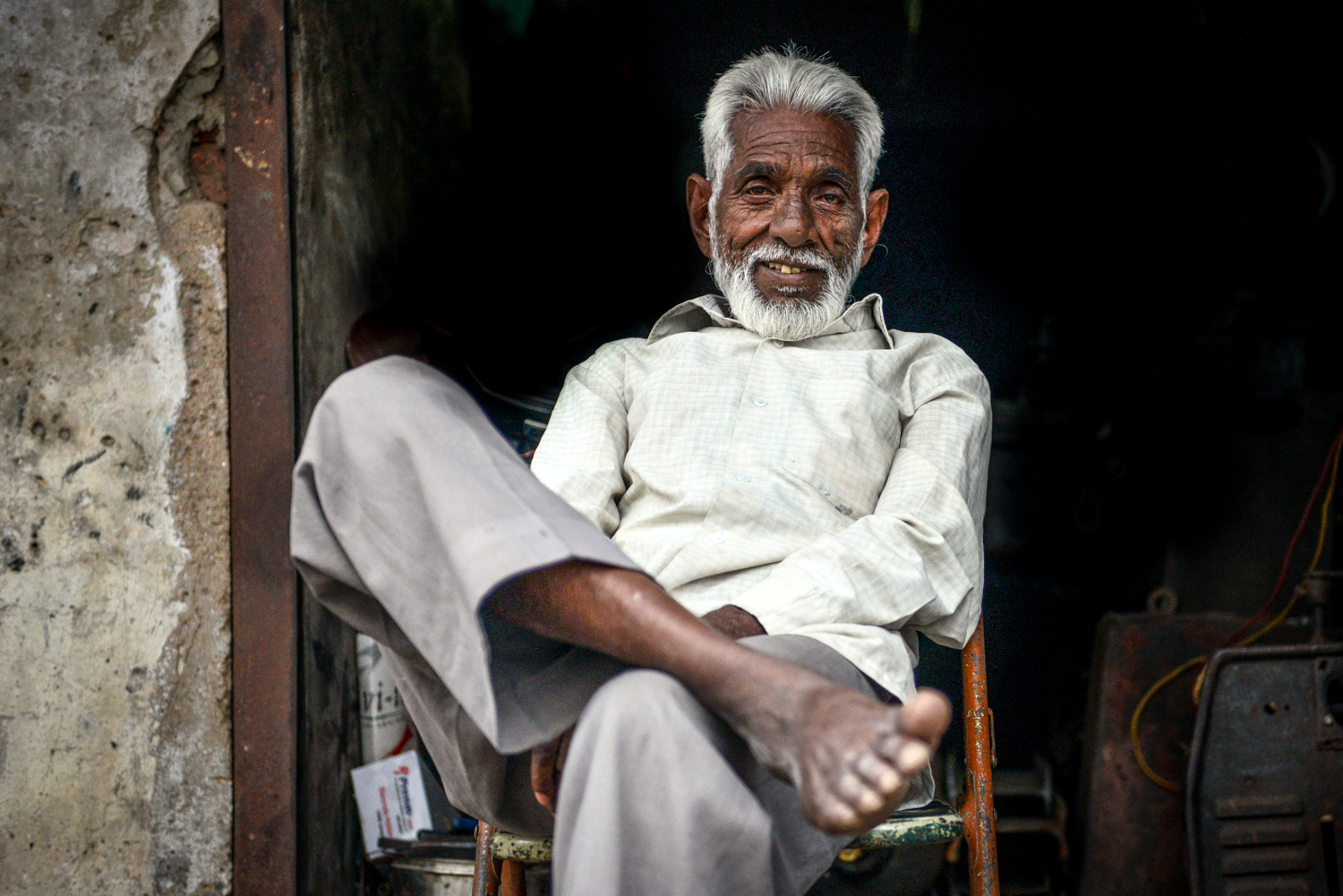 A man flashes a smile as sits in front of his workshop -Lucknow, India.