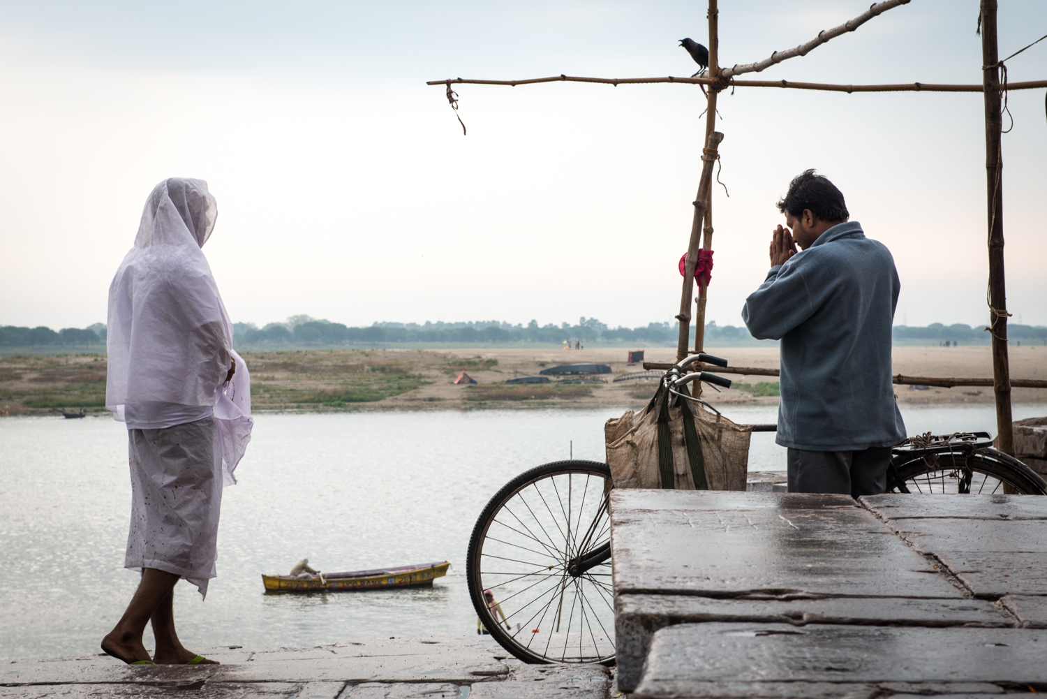 The man on the left wears white to respect the resent passing of a family member. The man on the bicycle pays respects with a 'Namaste' to the mourner,while a black crow looks on above - Varanasi, India.