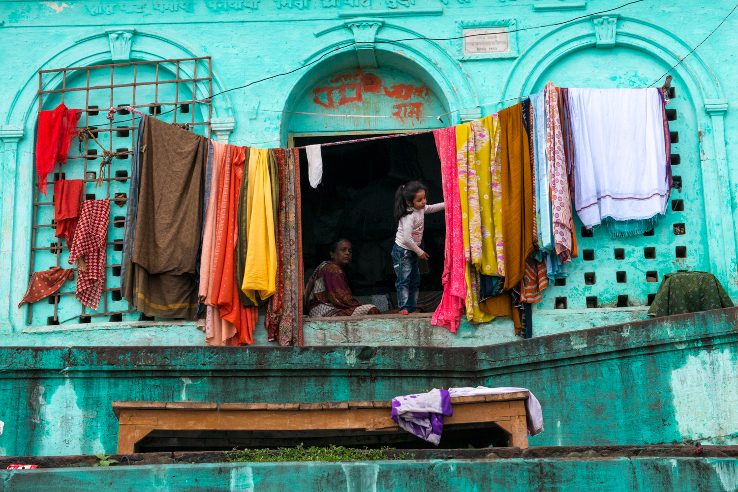 A young girl peaks out of her home to investigate a noise - Varanasi, India.