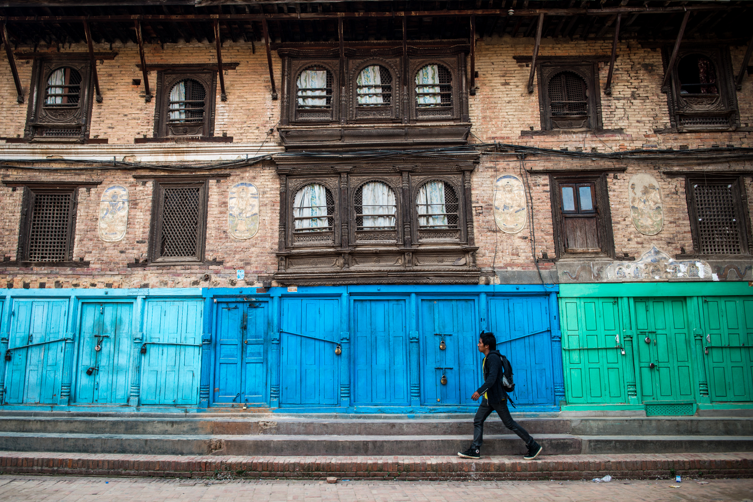 A man walks along closed shops near Durbar Square - Kathmandu, Nepal.