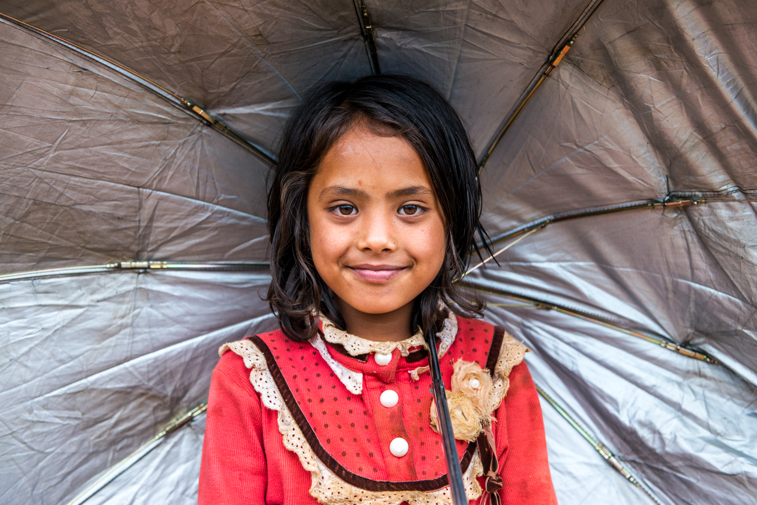 A girl flashes a smile under her umbrella - Khiping, Nepal.