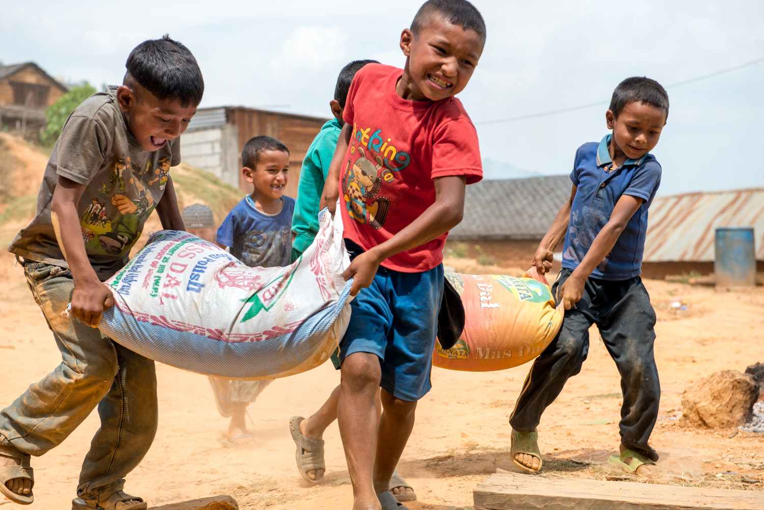 In times of crisis, children create an unlikely atmosphere of playfulness and resiliency. In Khari, Nepal the children insisted in helping us carry over 60 bags of 25kg of rice for the community of more than 200 families.
