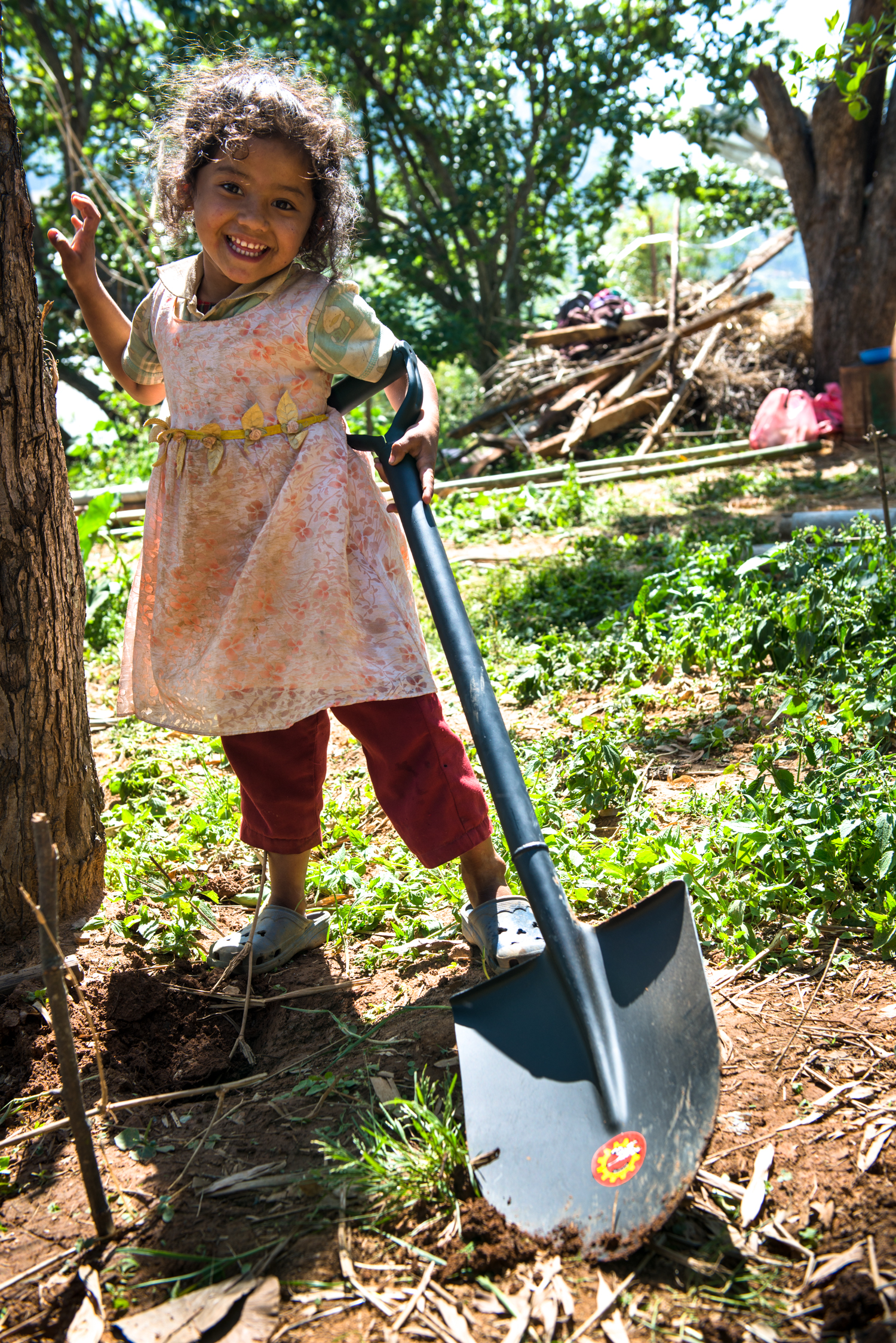 A cute nepalese girl playfully helps us shovel.