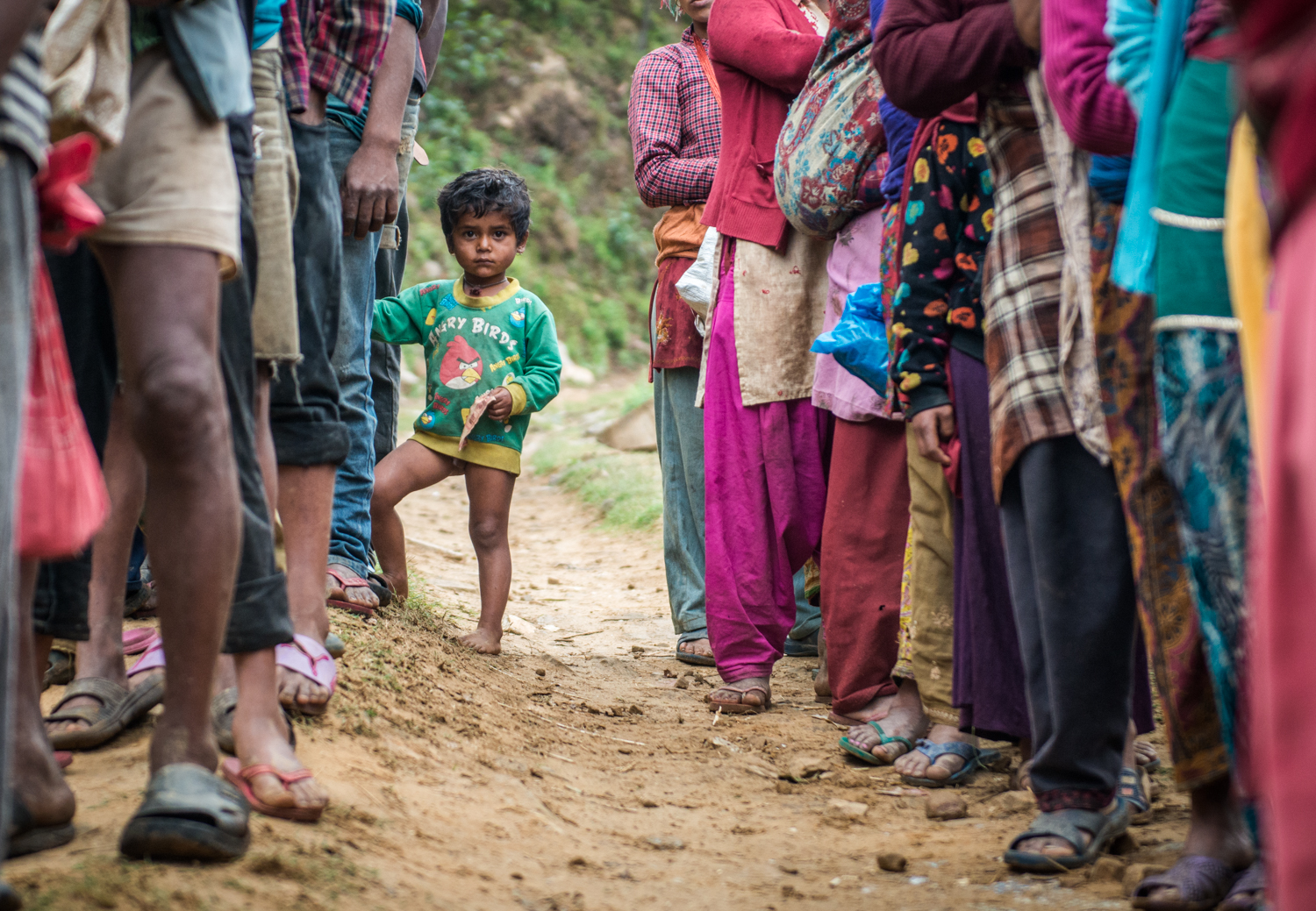 A boy stands in line alongside families to receive aid.