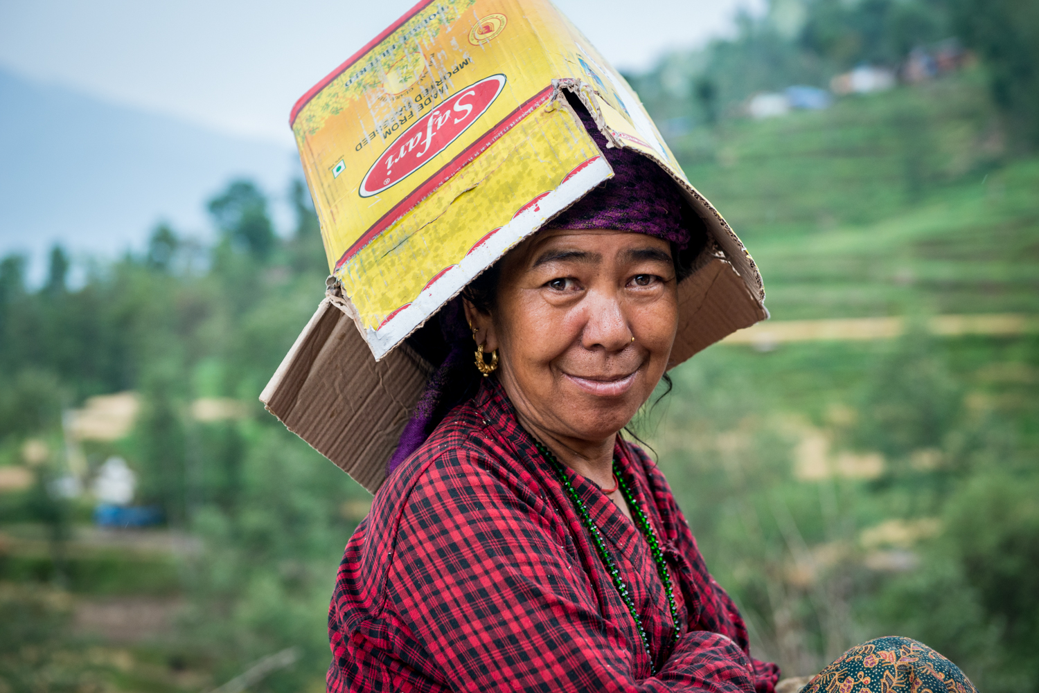A woman in sindhupalchok goofs around and wears a box to protect herself from the rain.