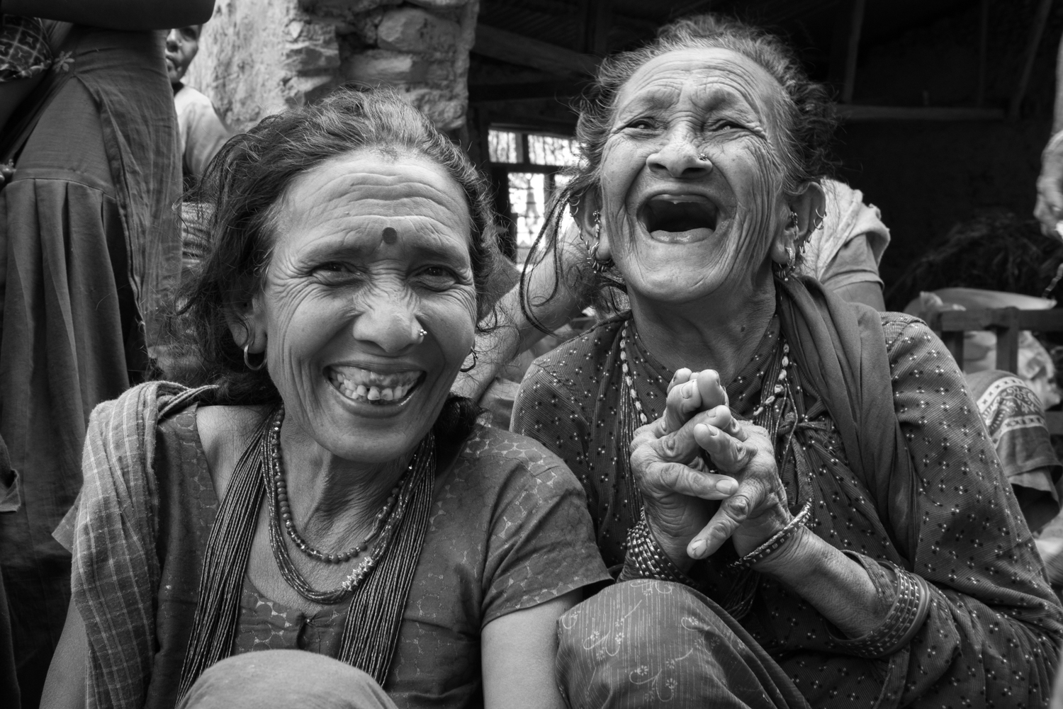 Two elder women chuckle as I show them images of themselves on my camera.