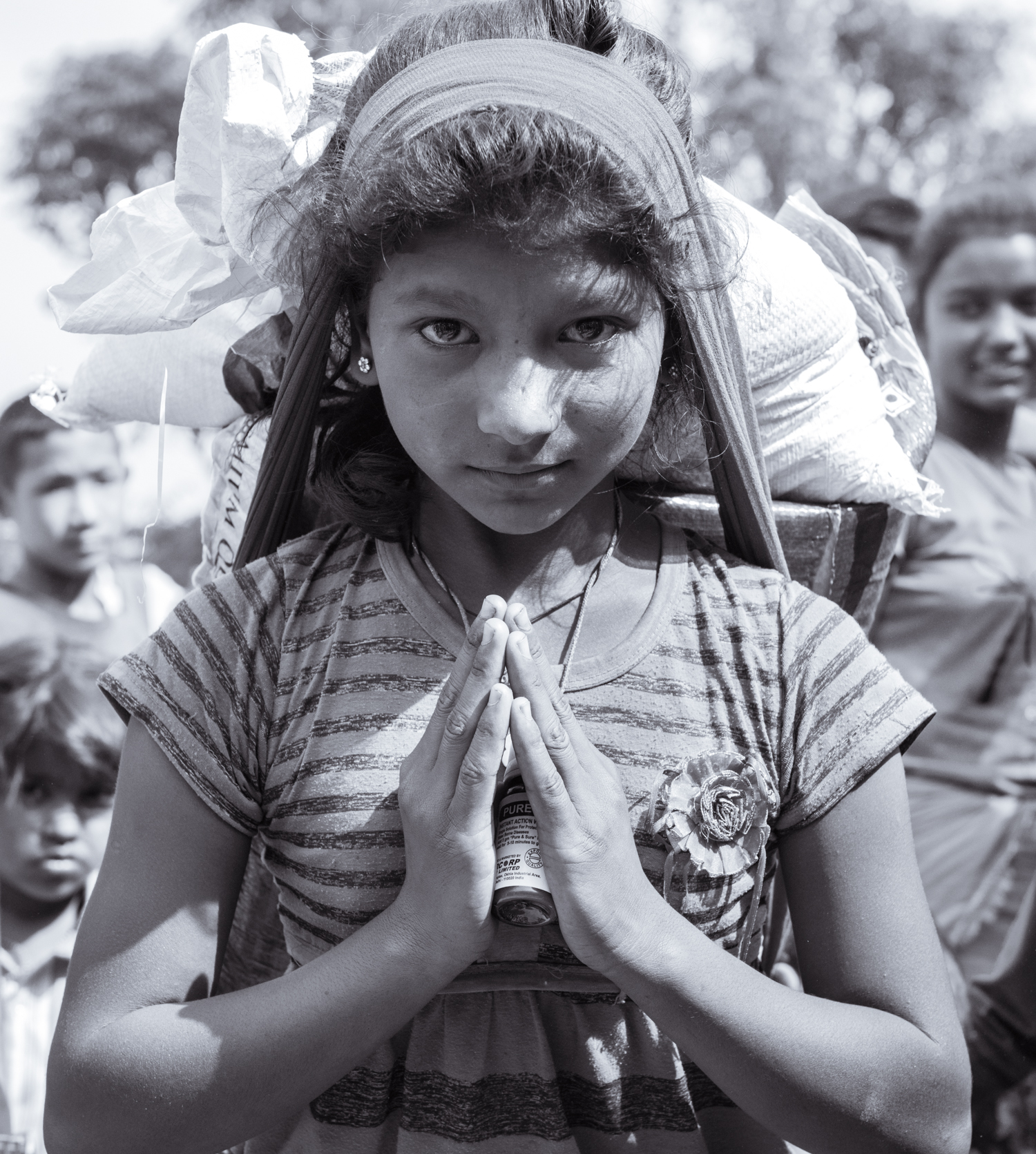 A poor girl greets with a 'Namaste' as we give her supplies to bring back to her family. She lost both of her parents in the earthquake and is currently living with her grandparents.