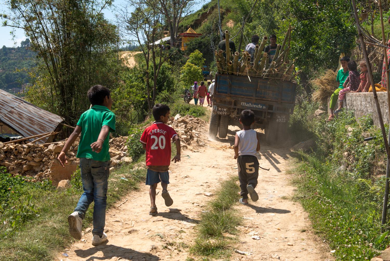 Children run after our supply trucks.
