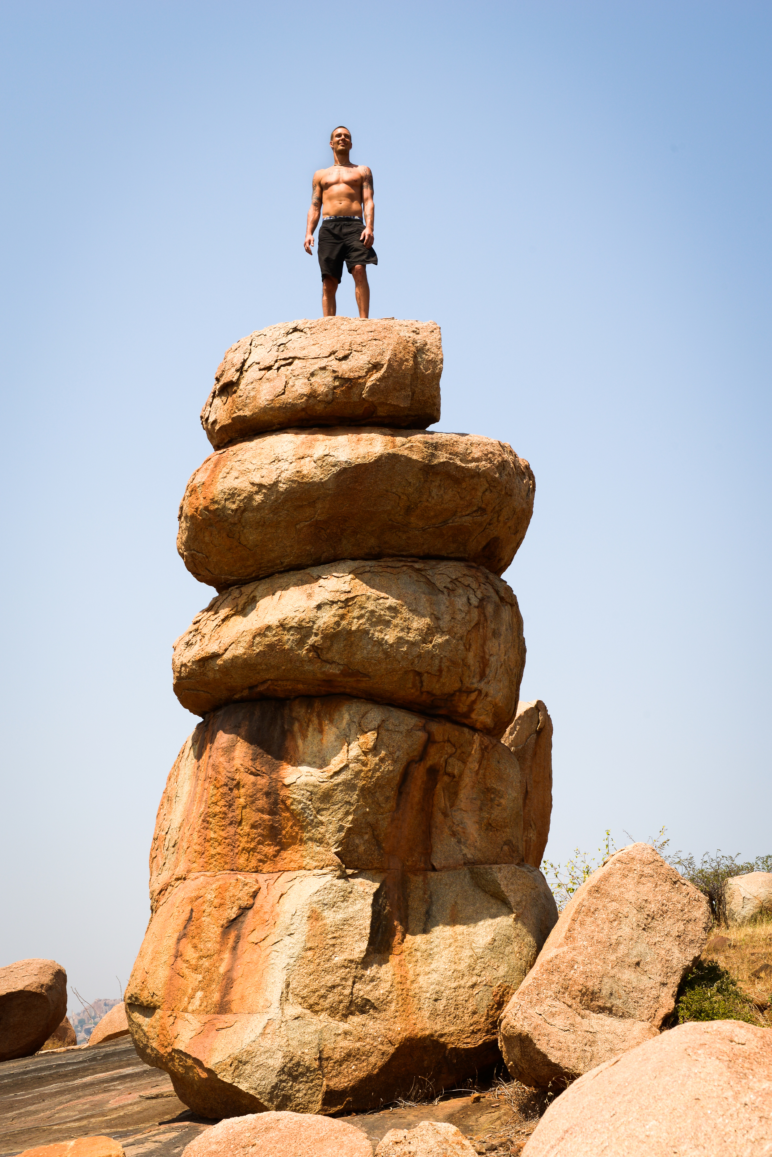 A climber stands a top of a stack of boulders - Hampi, India.
