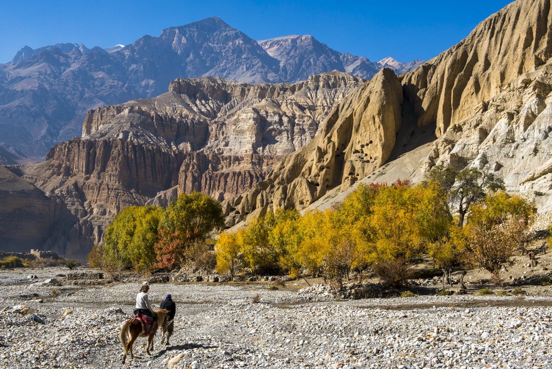 A trekker rides a horse in Upper Mustang Region in Nepal.