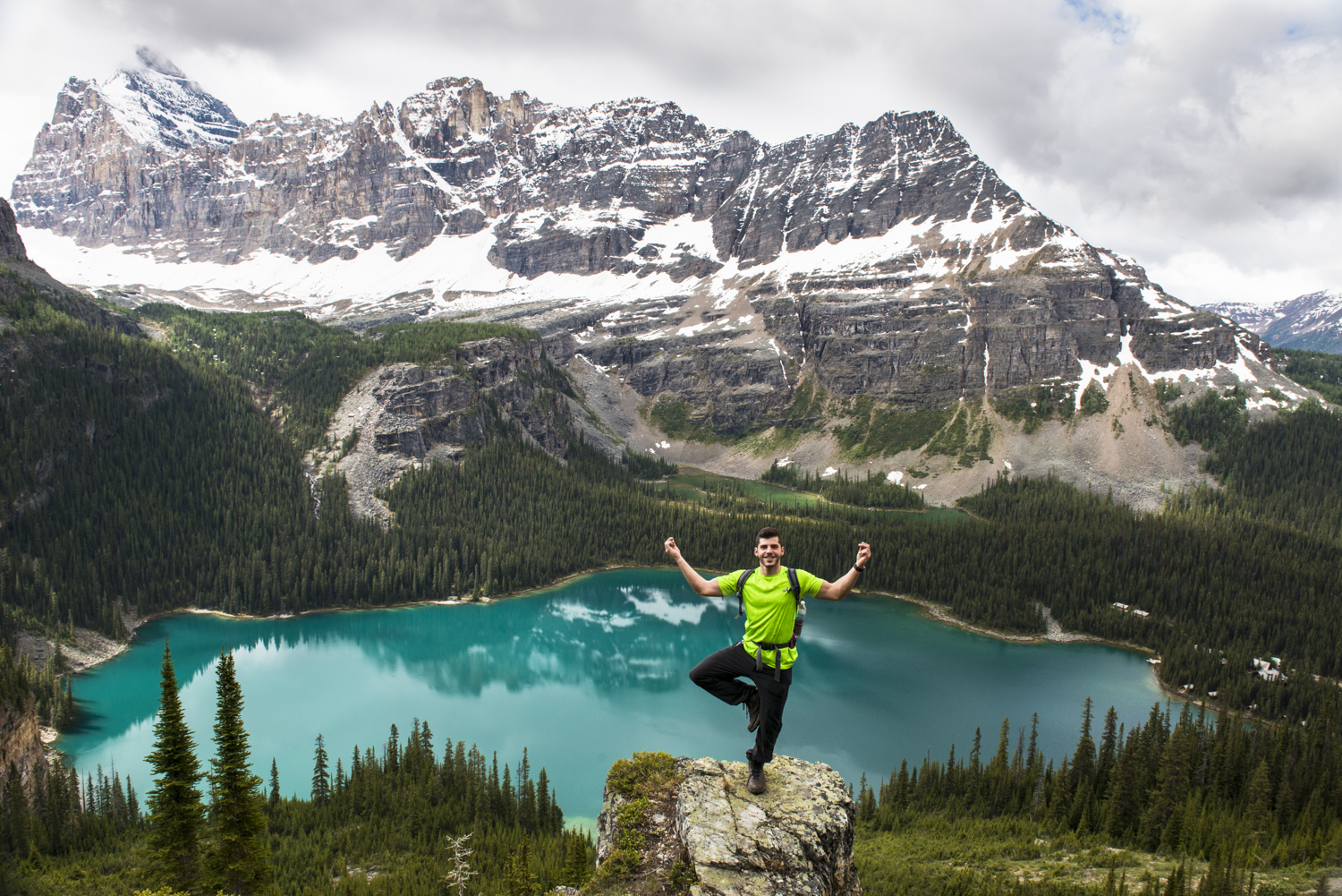 A hiker poses in front of Lake O'hara.