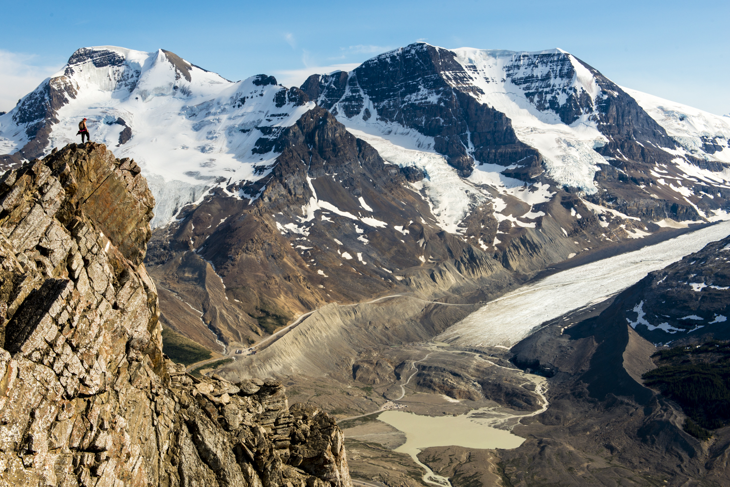 A hiker enjoys grandeur views of the Columbian Icefields and glaciers surrounding Mt Athabasca.