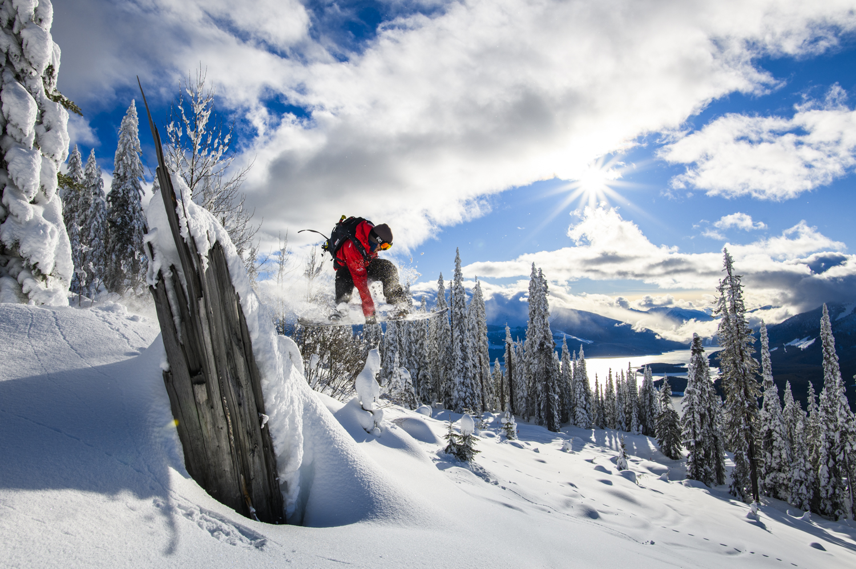 A snowboarder enjoys crisp winter powder near Mica Heli Lodge