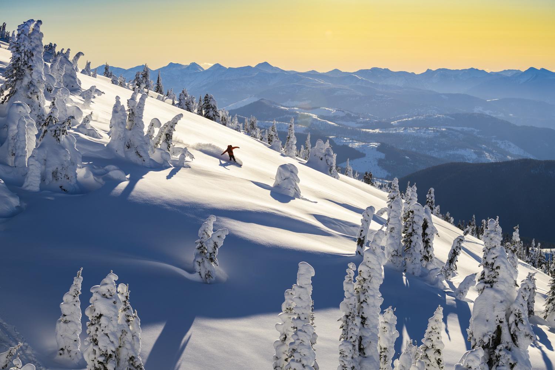 A snowboarder enjoys amazing powder and beautiful scenery ski touring near Grassy Hut, British Columbia